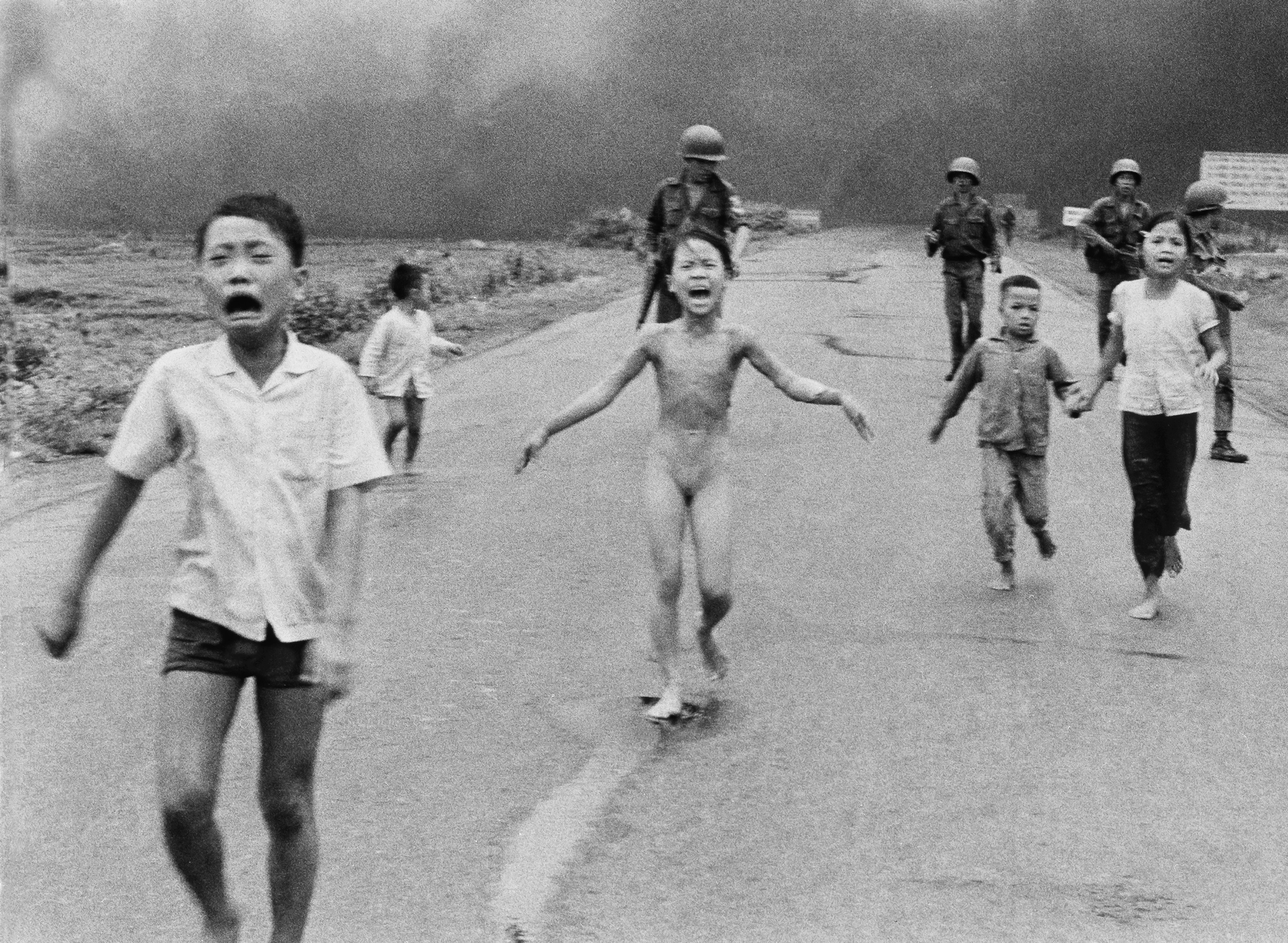 In this June 8, 1972 photo, South Vietnamese forces follow after terrified children, including 9-year-old Kim Phuc, center, as they run down Route 1 near Trang Bang after an aerial napalm attack on suspected Viet Cong hiding places.