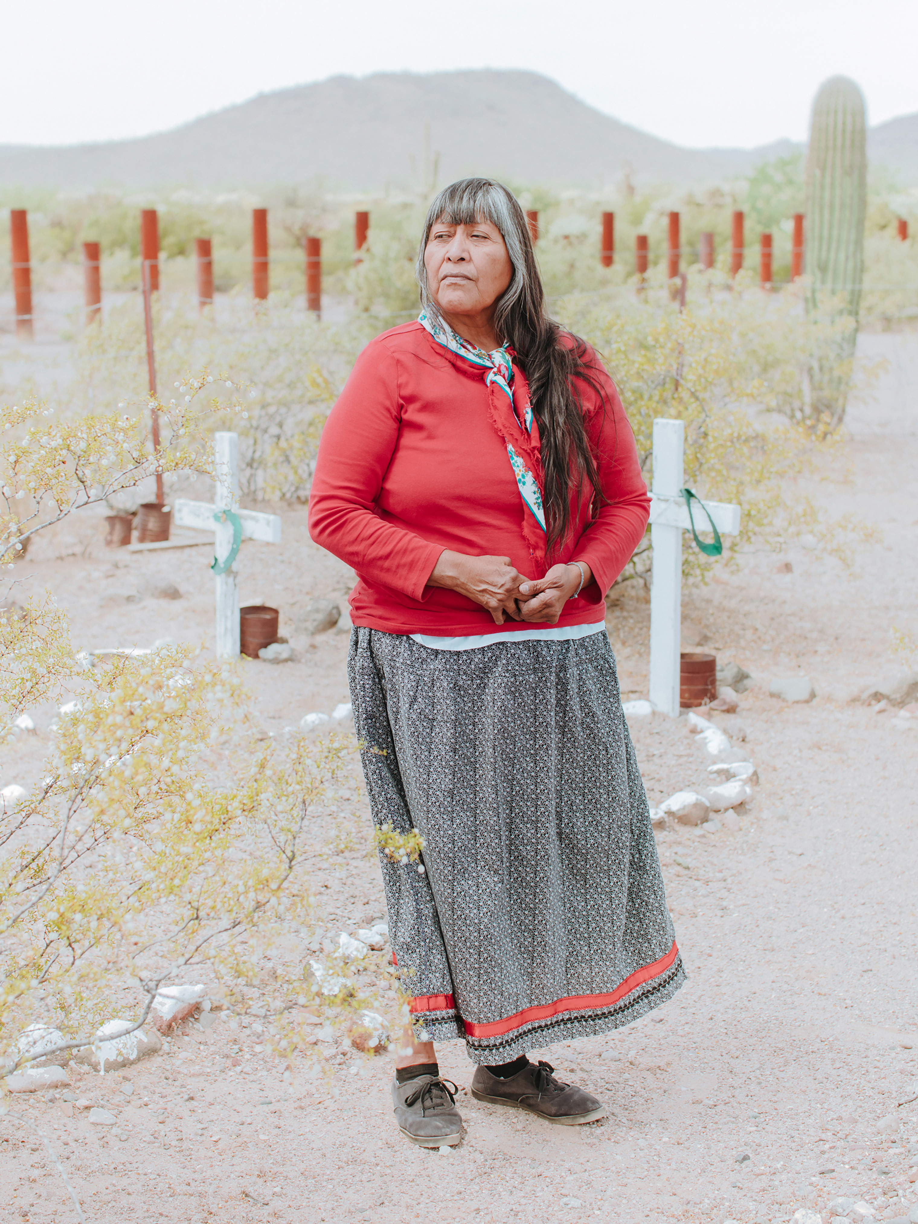 Ofelia Rivas poses in front of crosses her father made, marking the graves of two migrants who died from dehydration years before she was born in Tohono O'odham Nation, Ali Jek, Ariz.