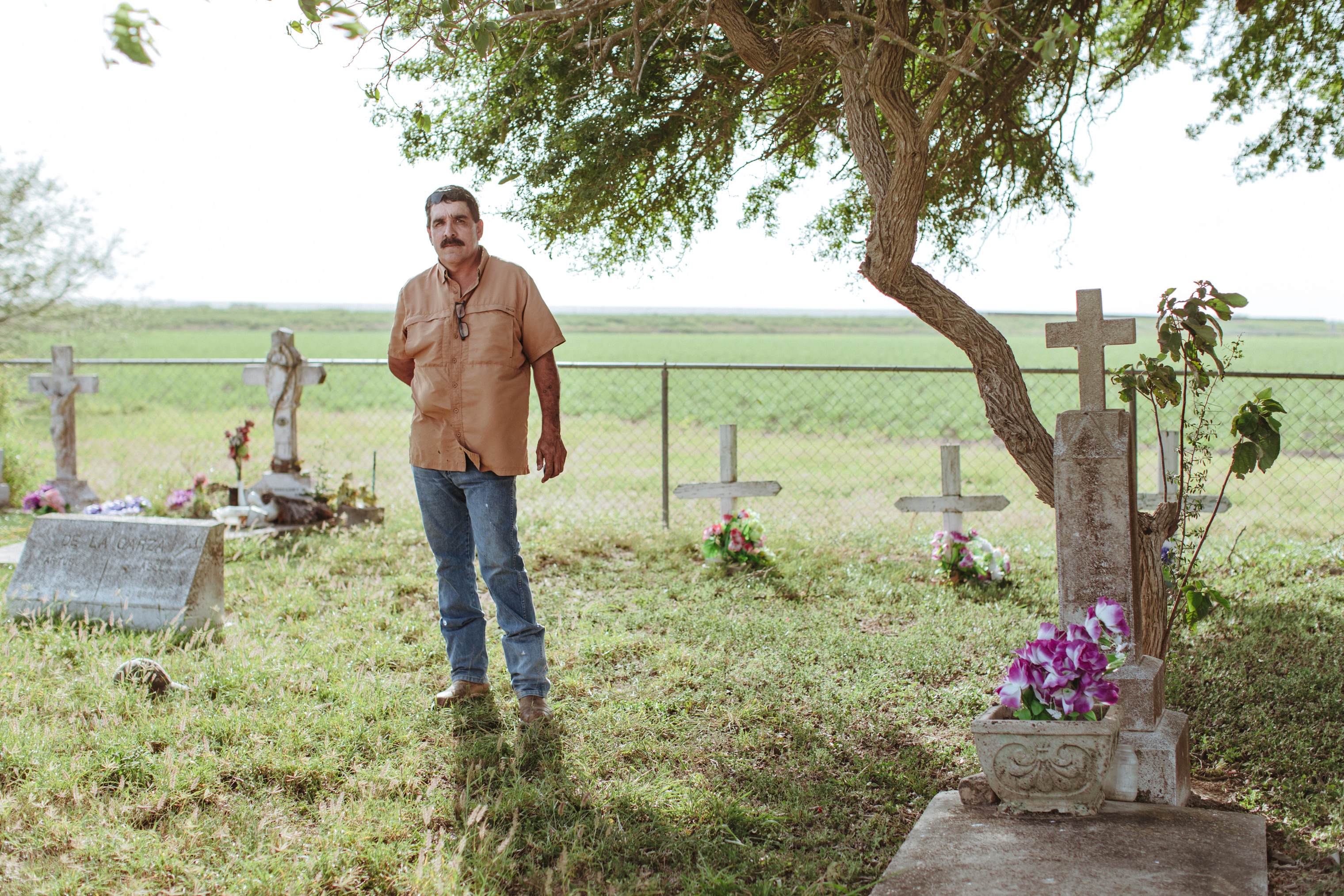 Charlie Vasquez at his family cemetery standing in front of the border fence in Donna, Texas.