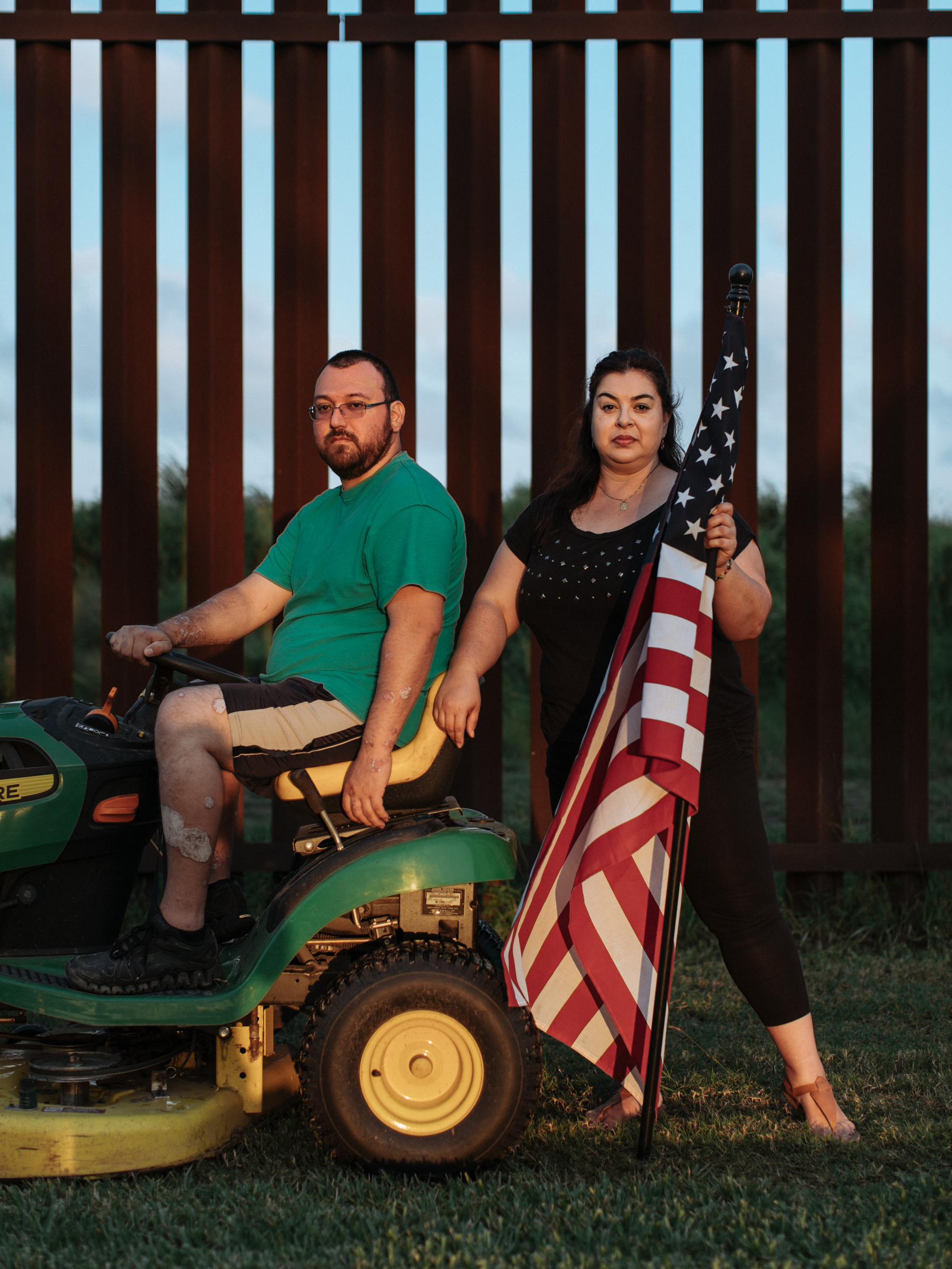 Tony and Melissa Solis stand before the border wall in their backyard, South Point, Texas.
