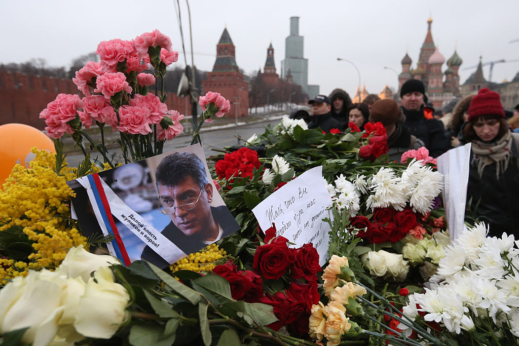 Mourners gather to place tributes at the site where Russian opposition leader and former Deputy Prime Minister Boris Nemtsov was killed on Bolshoi Moskvoretsky bridge near St. Basil cathedral, February 28, 2015 in central Moscow, Russia. Nemtsov, a fierce critic of President Vladimir Putin, was shot dead in central Moscow ahead of a major opposition rally.