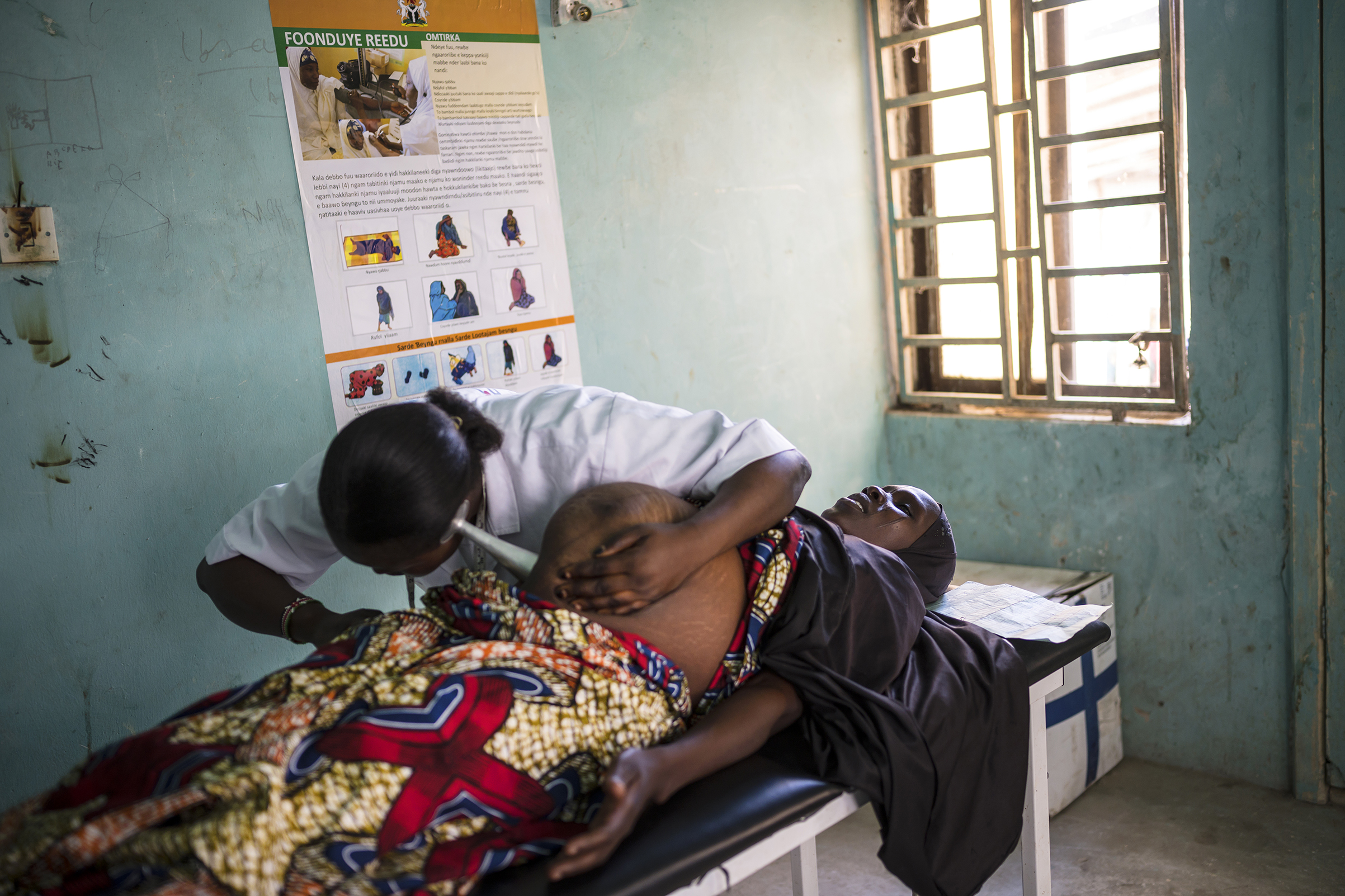 Midwife Topchin Job Goro, 28, checks Maryam Mohammed, 30, who is 38 weeks pregnant with her 8th child in the Ngala clinic