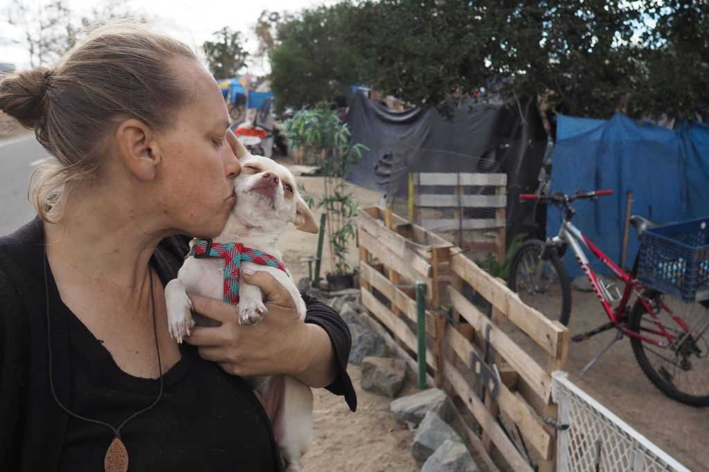 Homeless encampment resident Tammy Schuler kisses one of her pet dogs  beside a row of tents and tarps that line the Santa Ana River bicycle path, near Angel Stadium in Anaheim, California, January 25, 2018.
