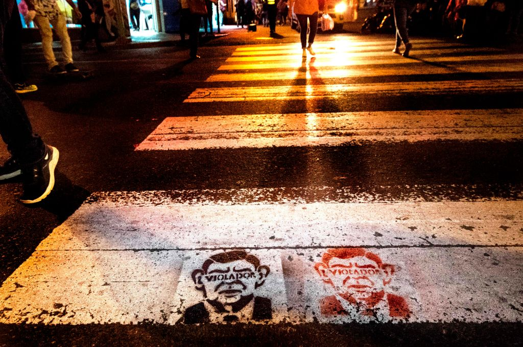 People walk through a pedestrian zone where graffiti that reads  rapist  is seen on the street over the face of the Nobel Peace Prize winner and Costa Rica's former President, Oscar Arias, who was accused of sexual assault. San Jose, Costa Rica, Feb. 8, 2019.