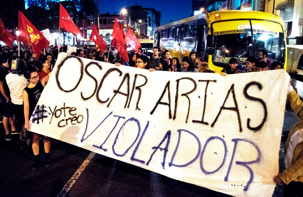 People protest, holding a sign that read  Oscar Arias rapist,  against Nobel Peace Prize winner and former Costa Rican president Oscar Arias, who was accused of sexual assault in San Jose, Costa Rica February 8, 2019.