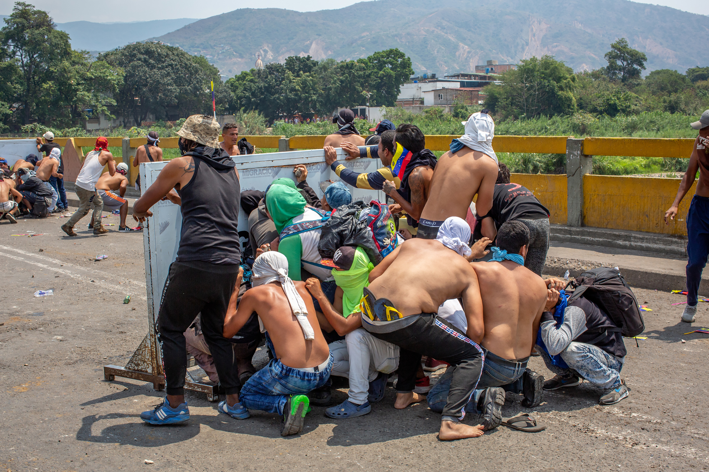 A group of demonstrators take cover during a clash with Venezuelan national police officers on the Simón Bolívar International Bridge, which connects Colombia and Venezuela, near Cúcuta, on Feb. 23, 2019.