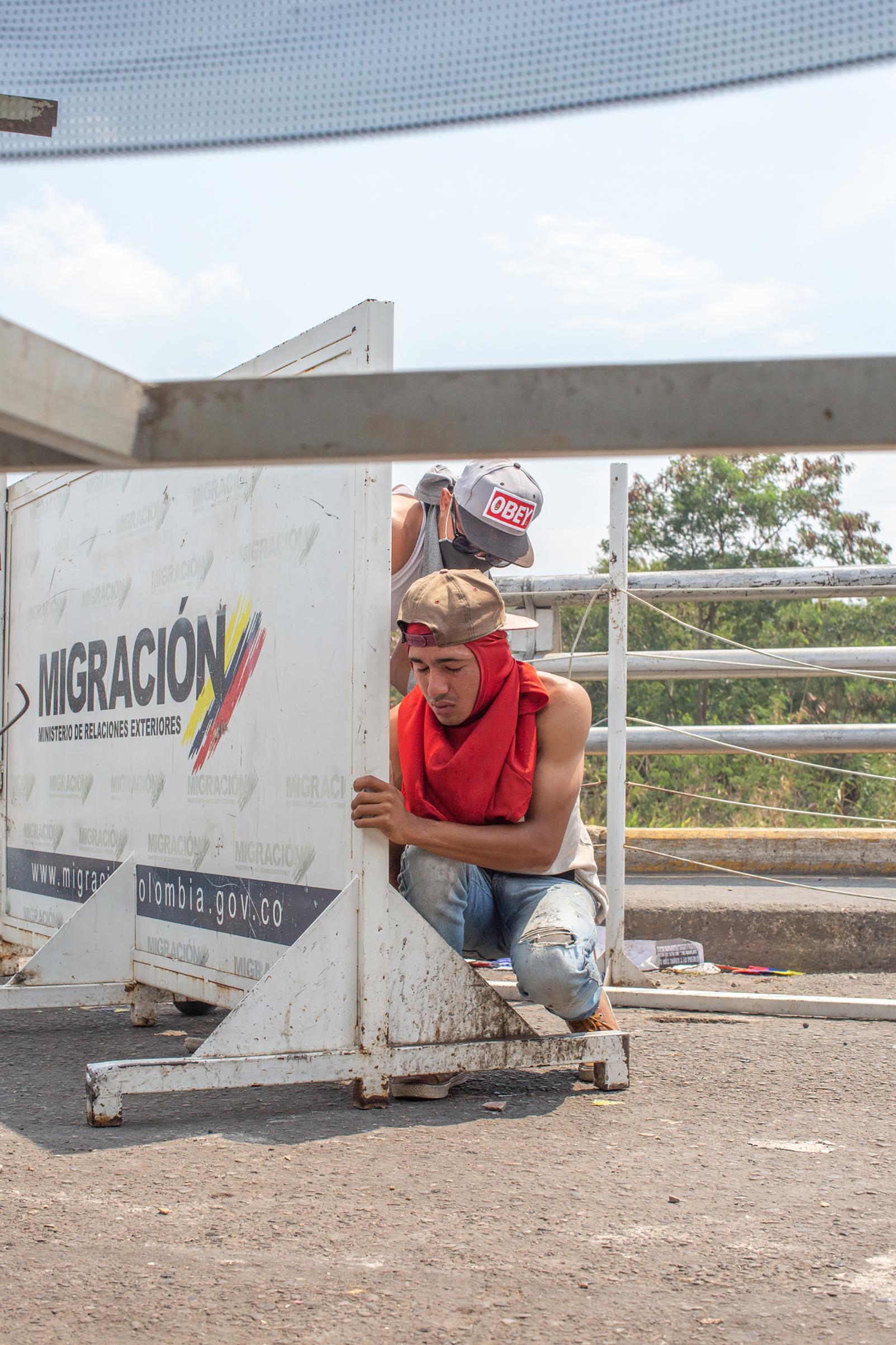 Two demonstrators take cover on the Simón Bolívar International Bridge before the clash on Feb. 23, 2019.