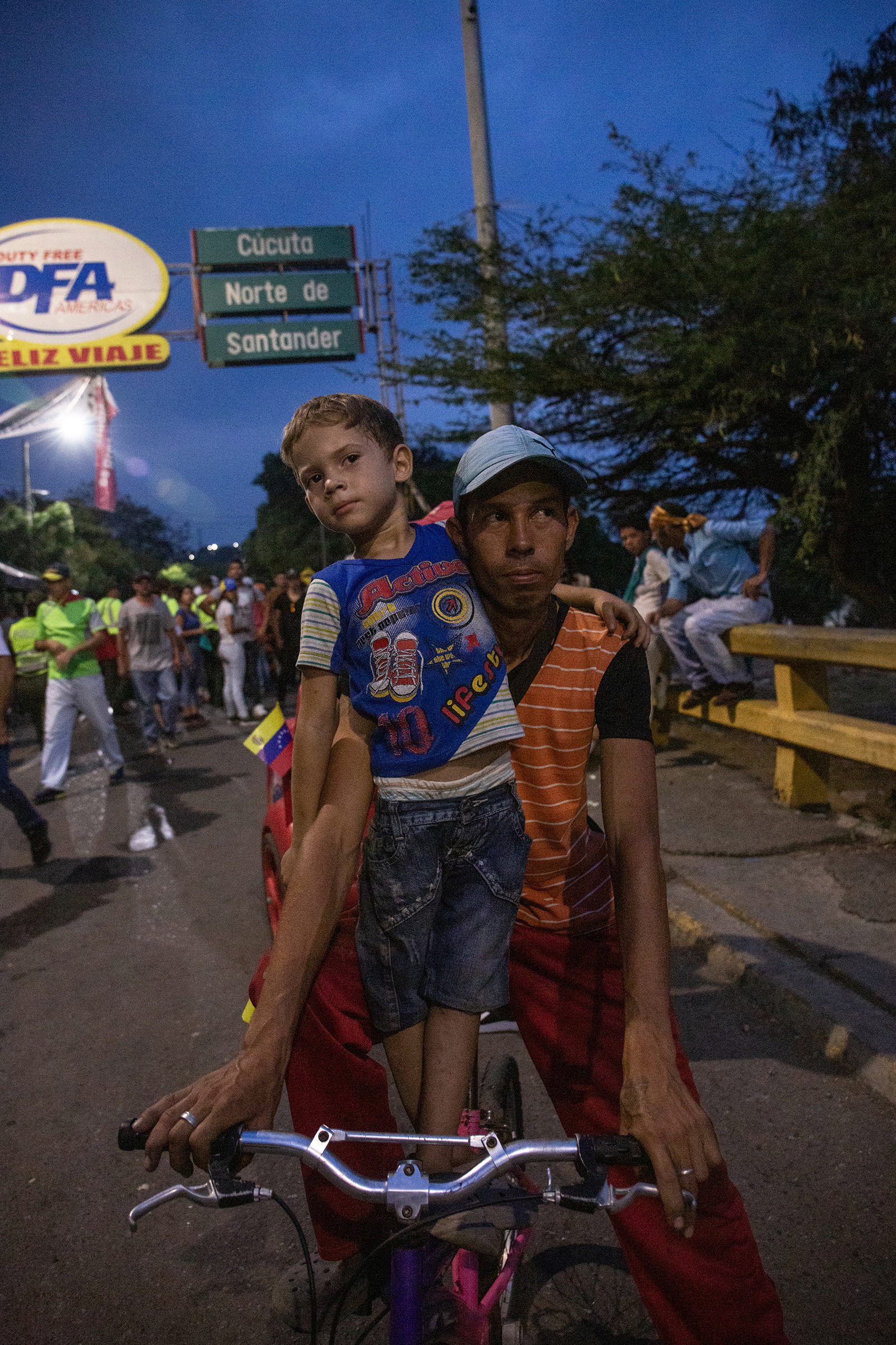 A man and boy watch demonstrators on the Ureña Bridge, which connects Colombia and Venezuela, on Feb. 23, 2019.