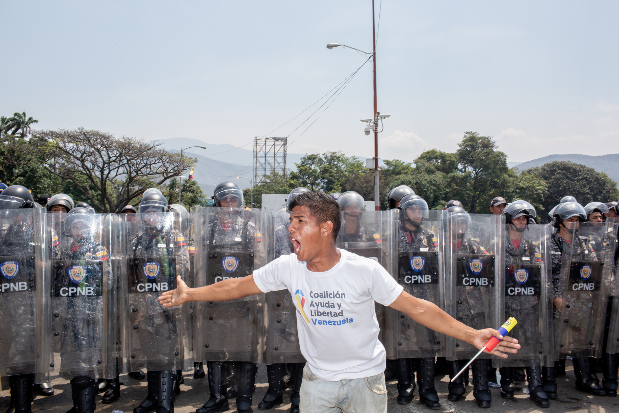 A demonstrator yells in front of Venezuelan national police officers before a clash on the bridge.