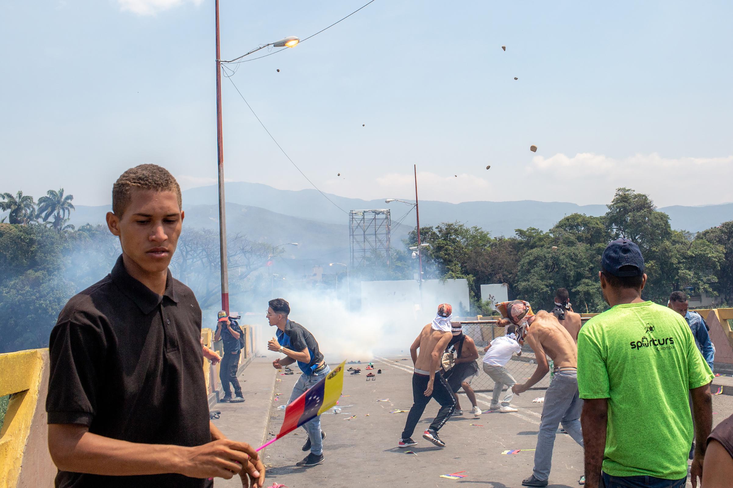 Demonstrators hurl rocks toward Venezuelan national police officers.