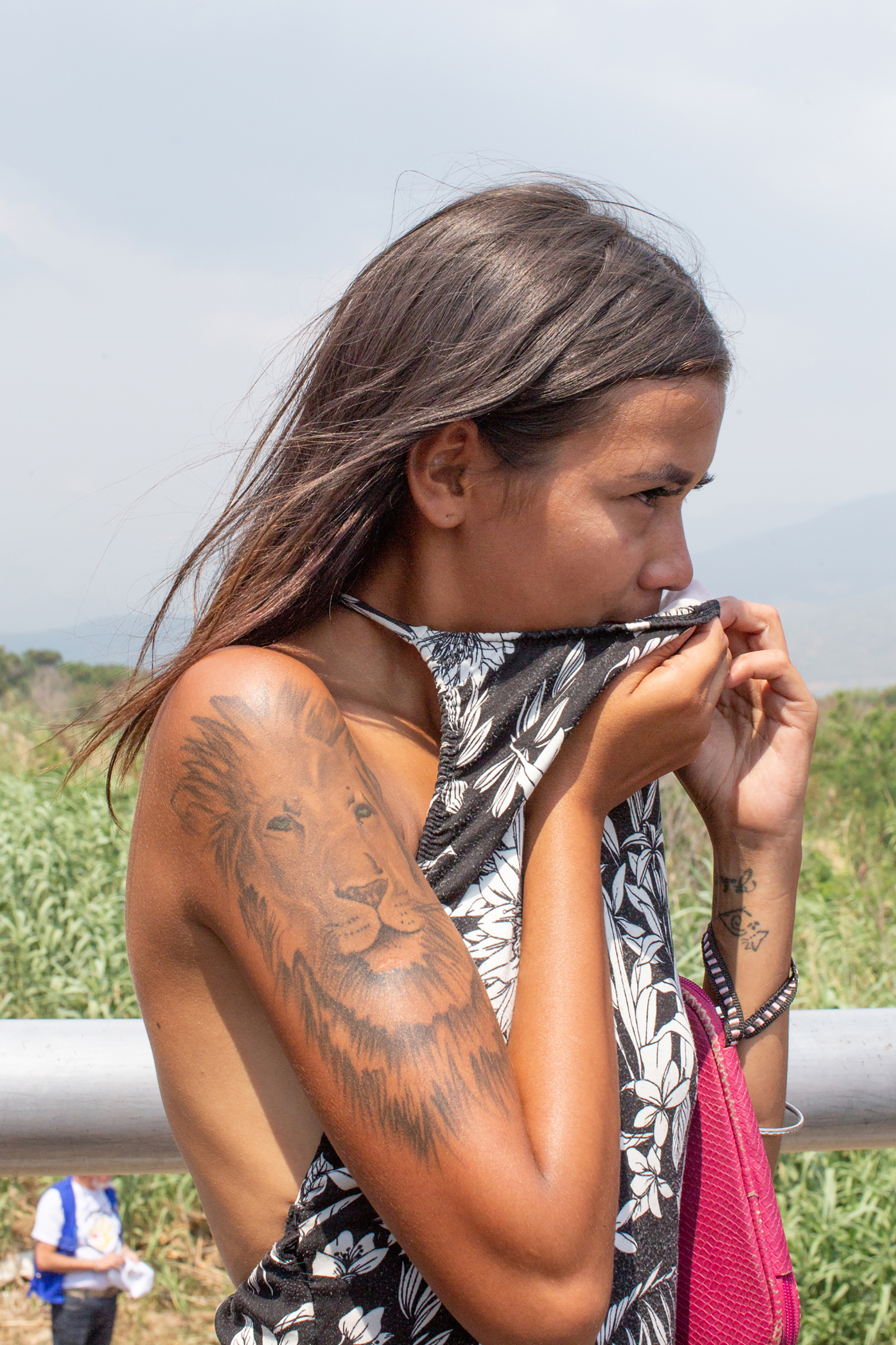 A girl covers her mouth from the choking tear gas and watches from the back of the Simón Bolívar International Bridge, which connects Colombia and Venezuela, near Cúcuta, on Feb. 23, 2019.