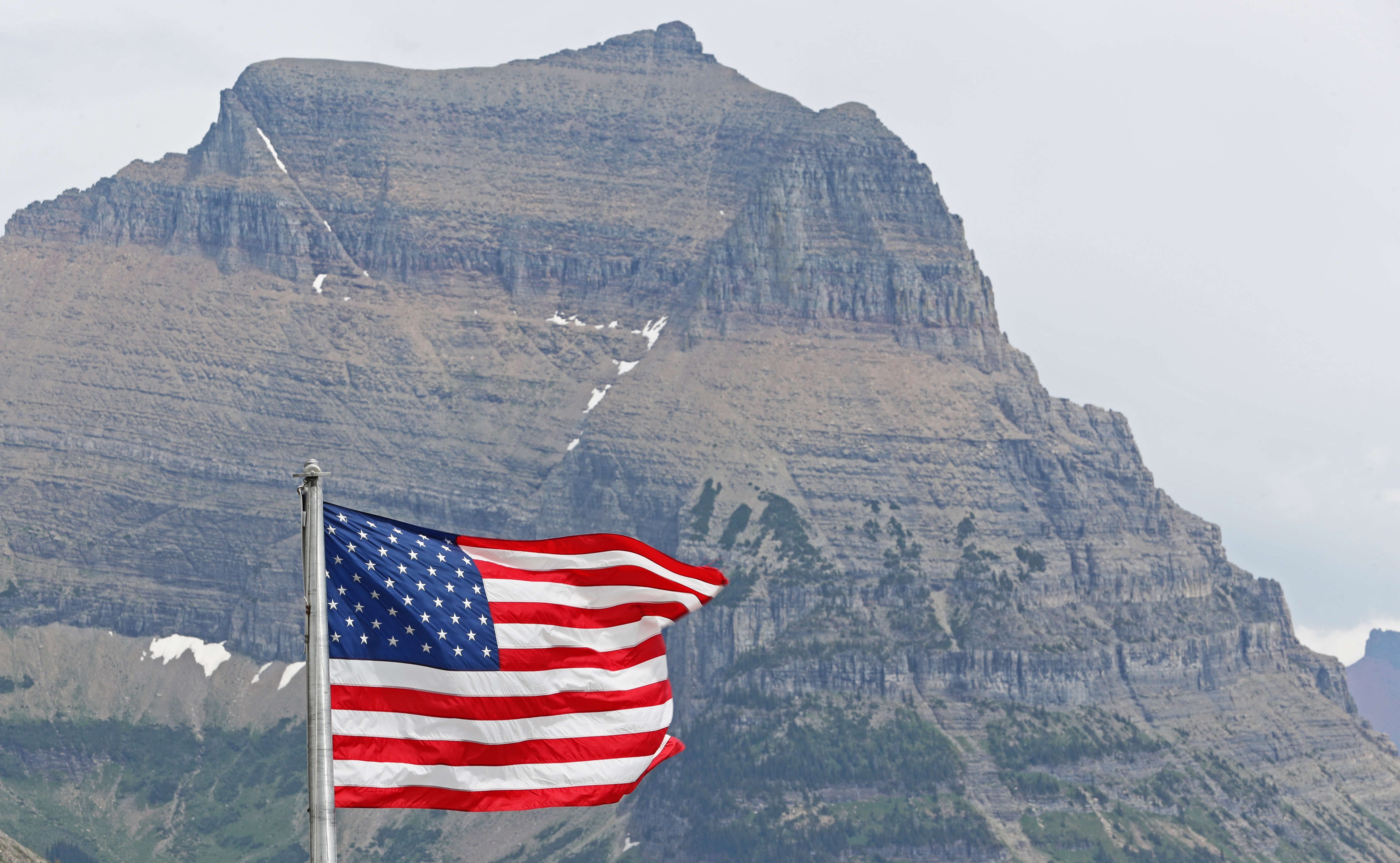An American flag flies in front of the Logan Pass Visitor Center in Glacier National Park on July 26, 2018 in West Glacier, Montana.