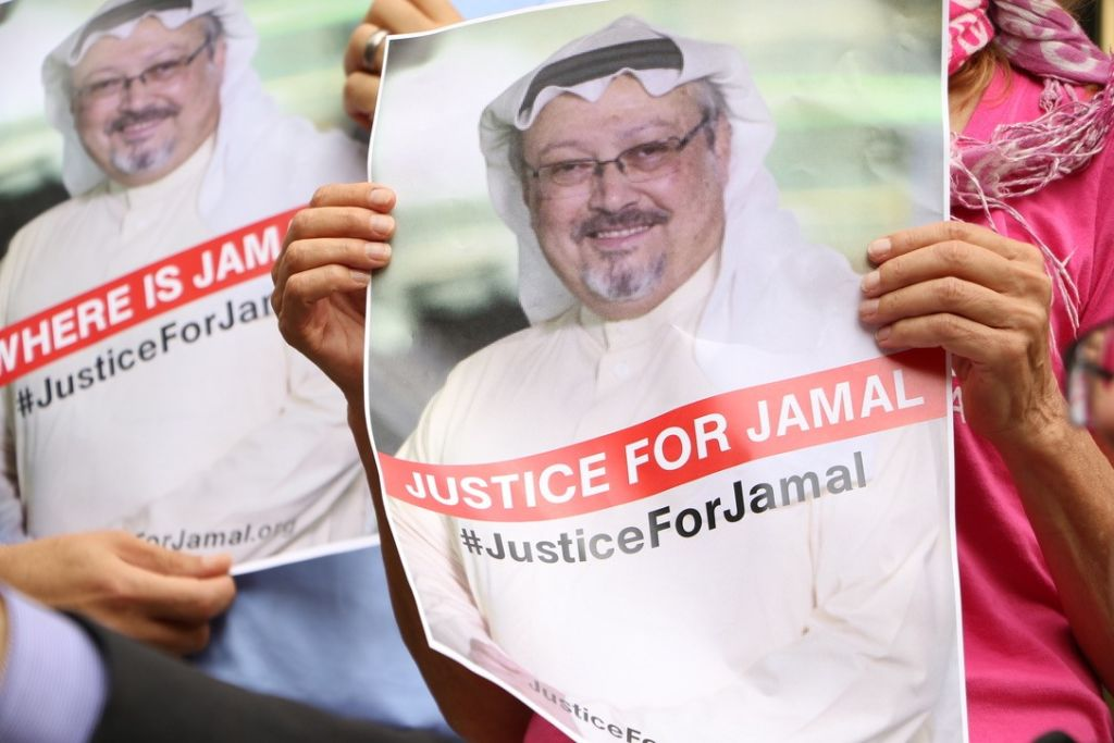 A member of the Organization 'Justice for Jamal Khashoggi' holds a picture of the slain journalist during a news conference in front of The Washington Post headquarters in Washington D.C. on Oct. 10, 2018.