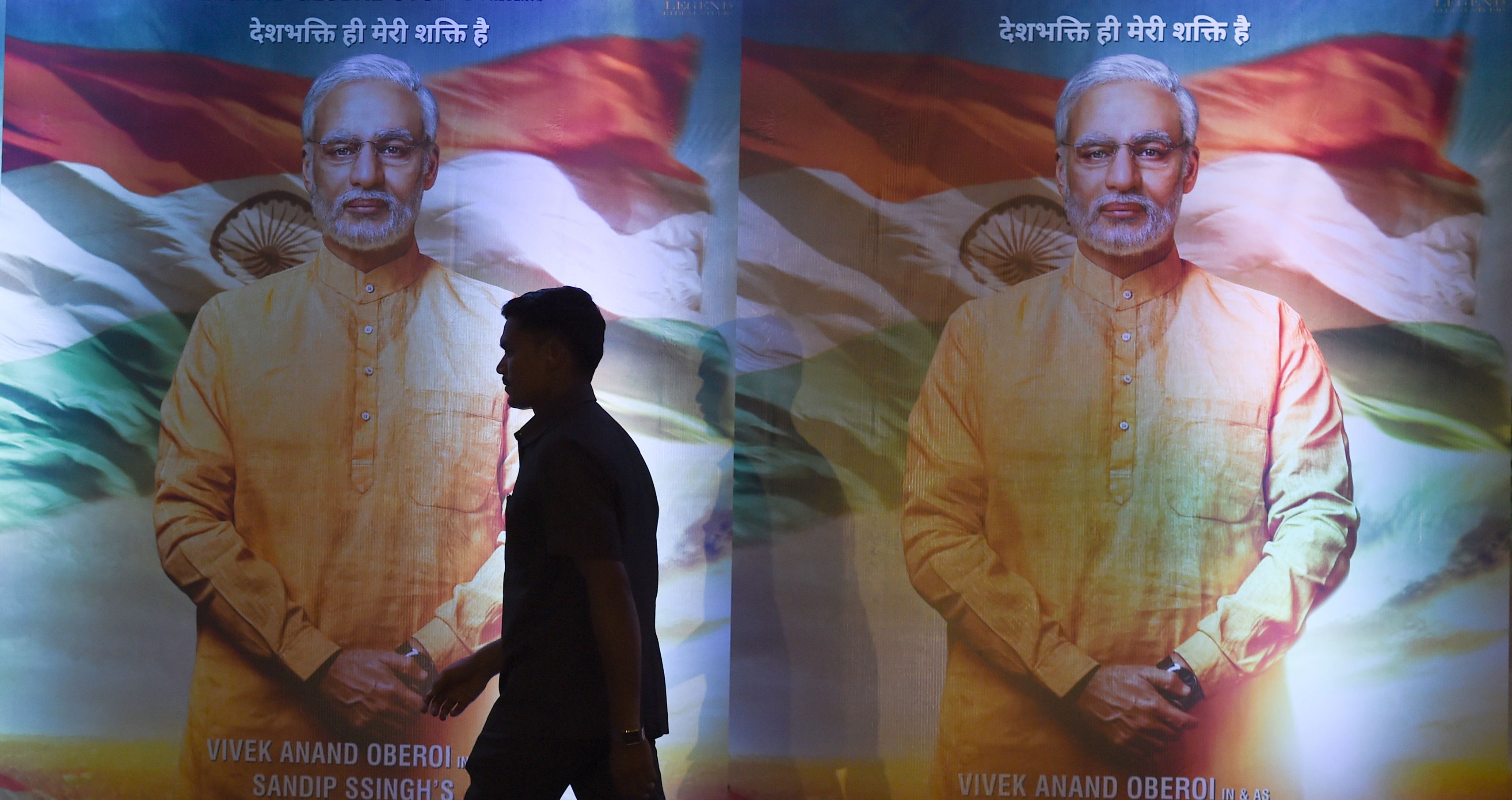 An Indian man walks in front of posters of the upcoming Bollywood film  PM Narendra Modi  - a biopic on Indian Prime Minister Narendra Modi
