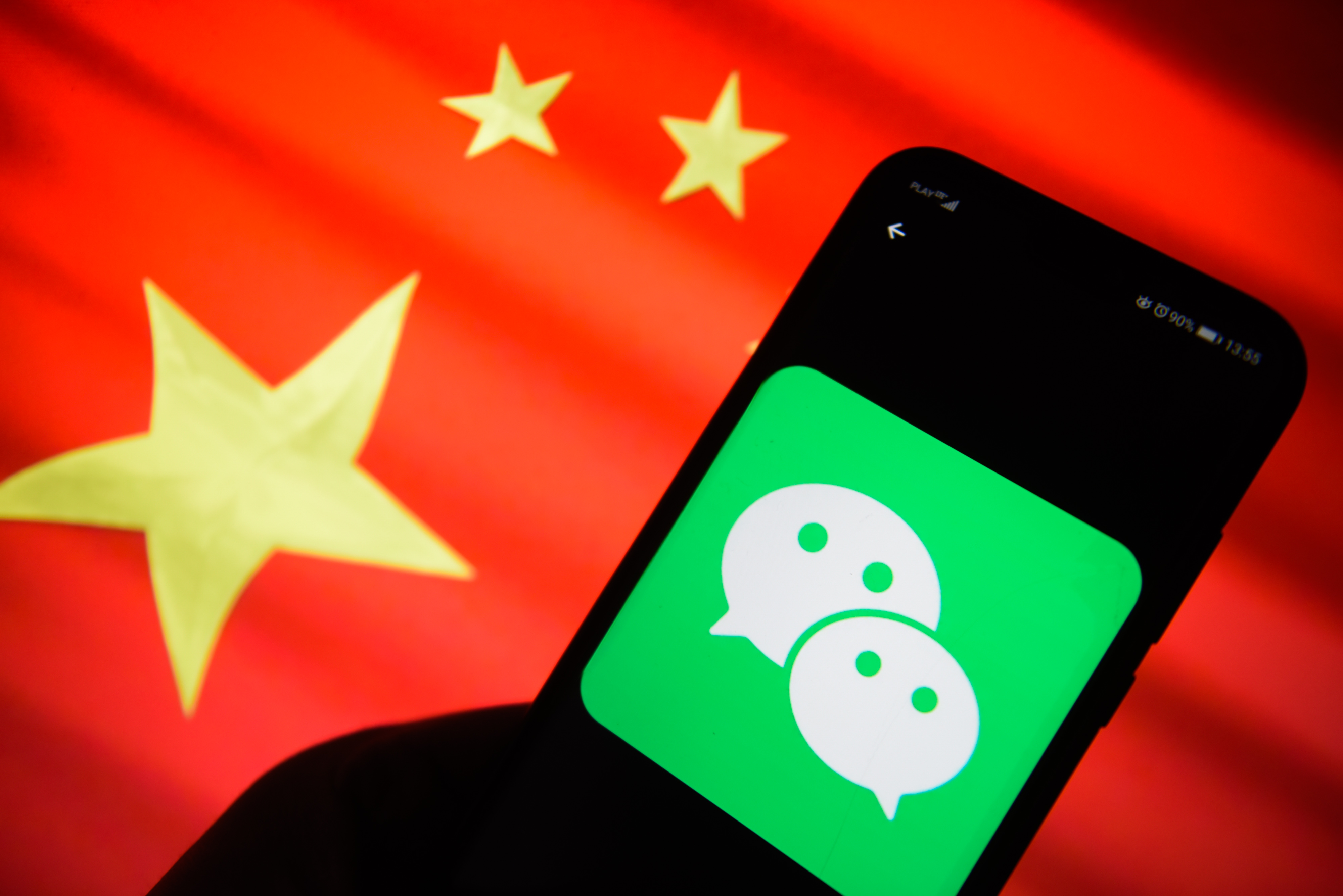 The WeChat logo is seen on a mobile phone with China's flag in the background.
