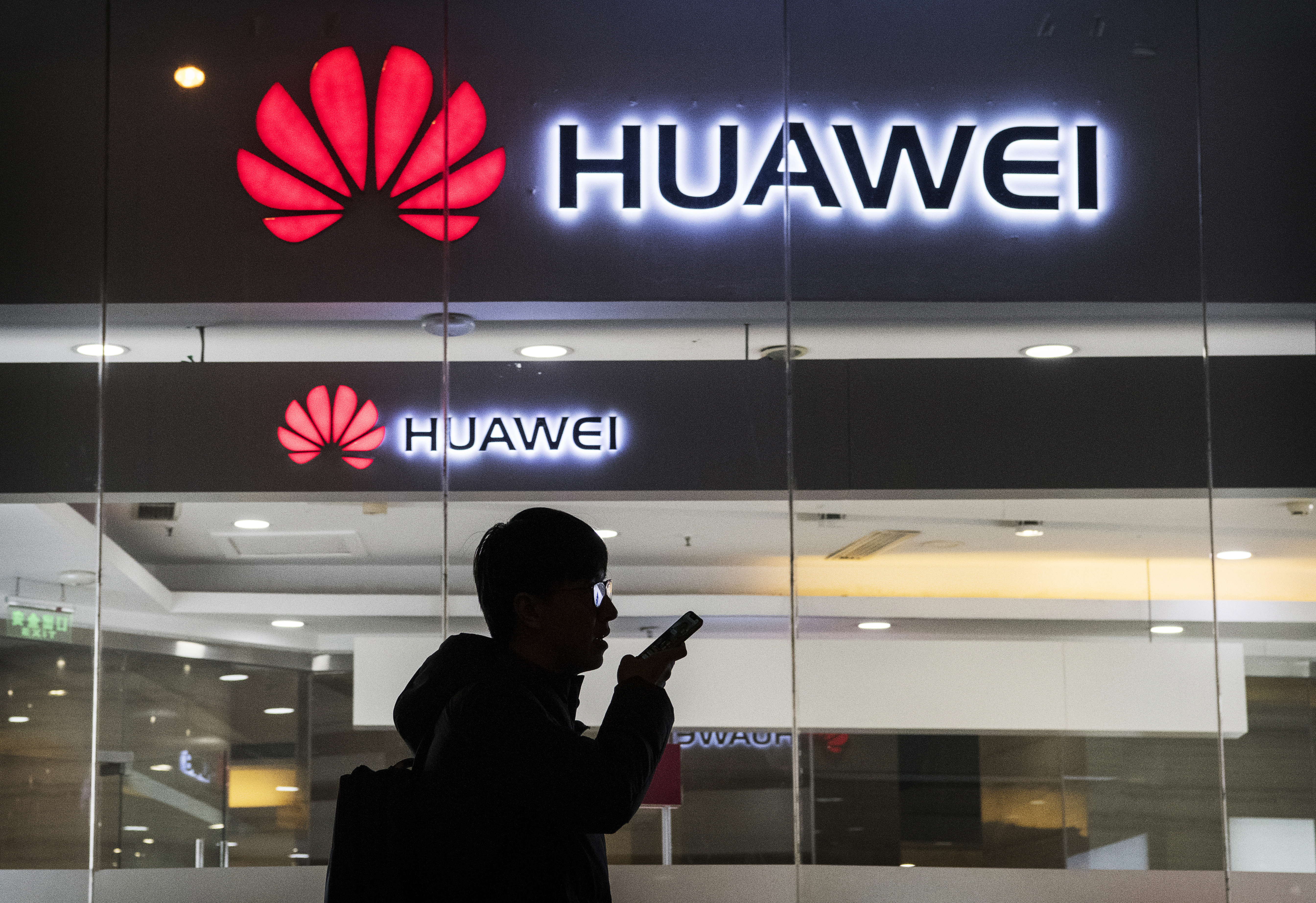 A pedestrian talks on the phone while walking past a Huawei store in Beijing on Jan. 29.