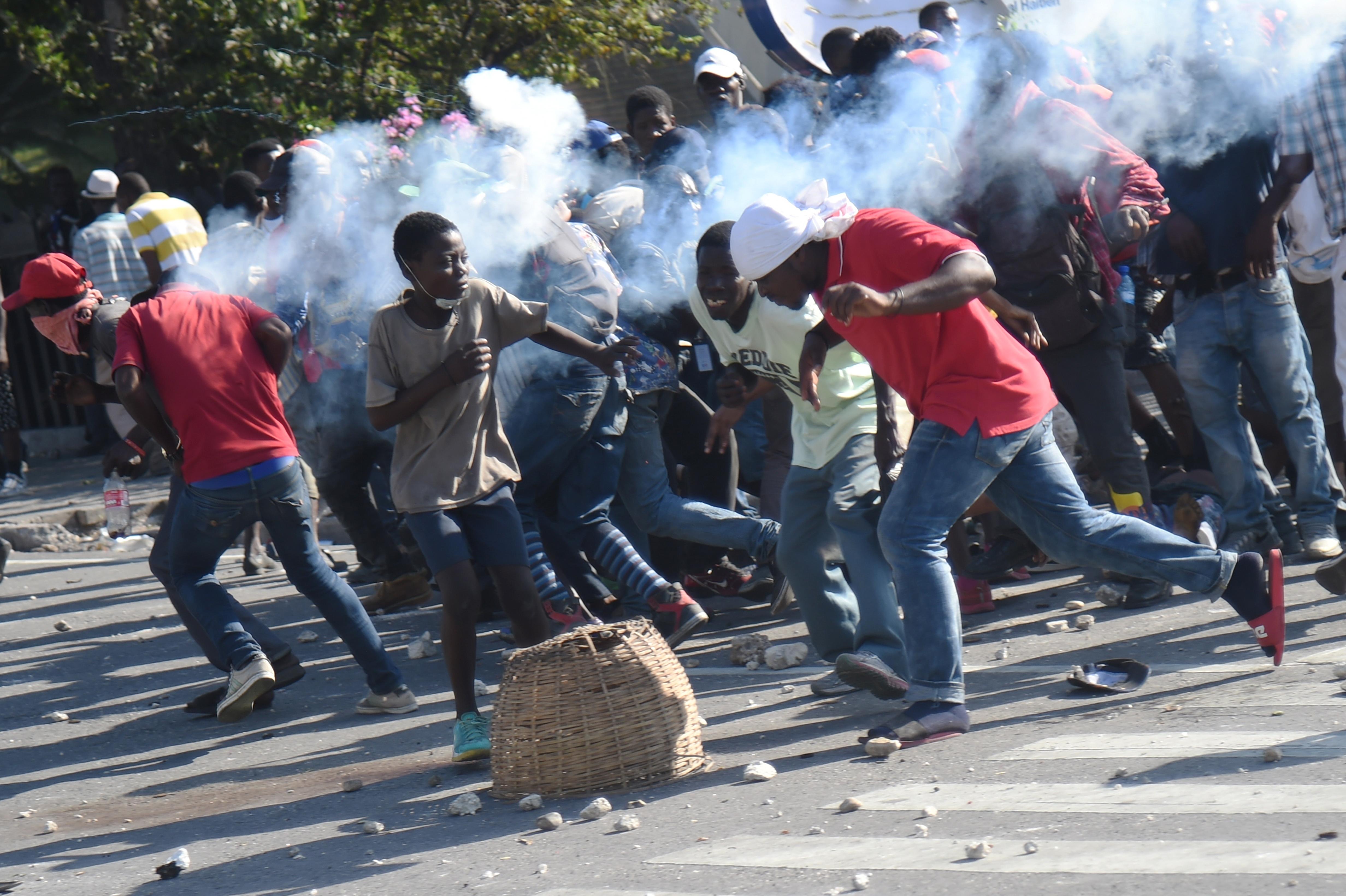 Protesters run as police fire tear gas in Port-au-Prince, Haiti, on Feb. 13.