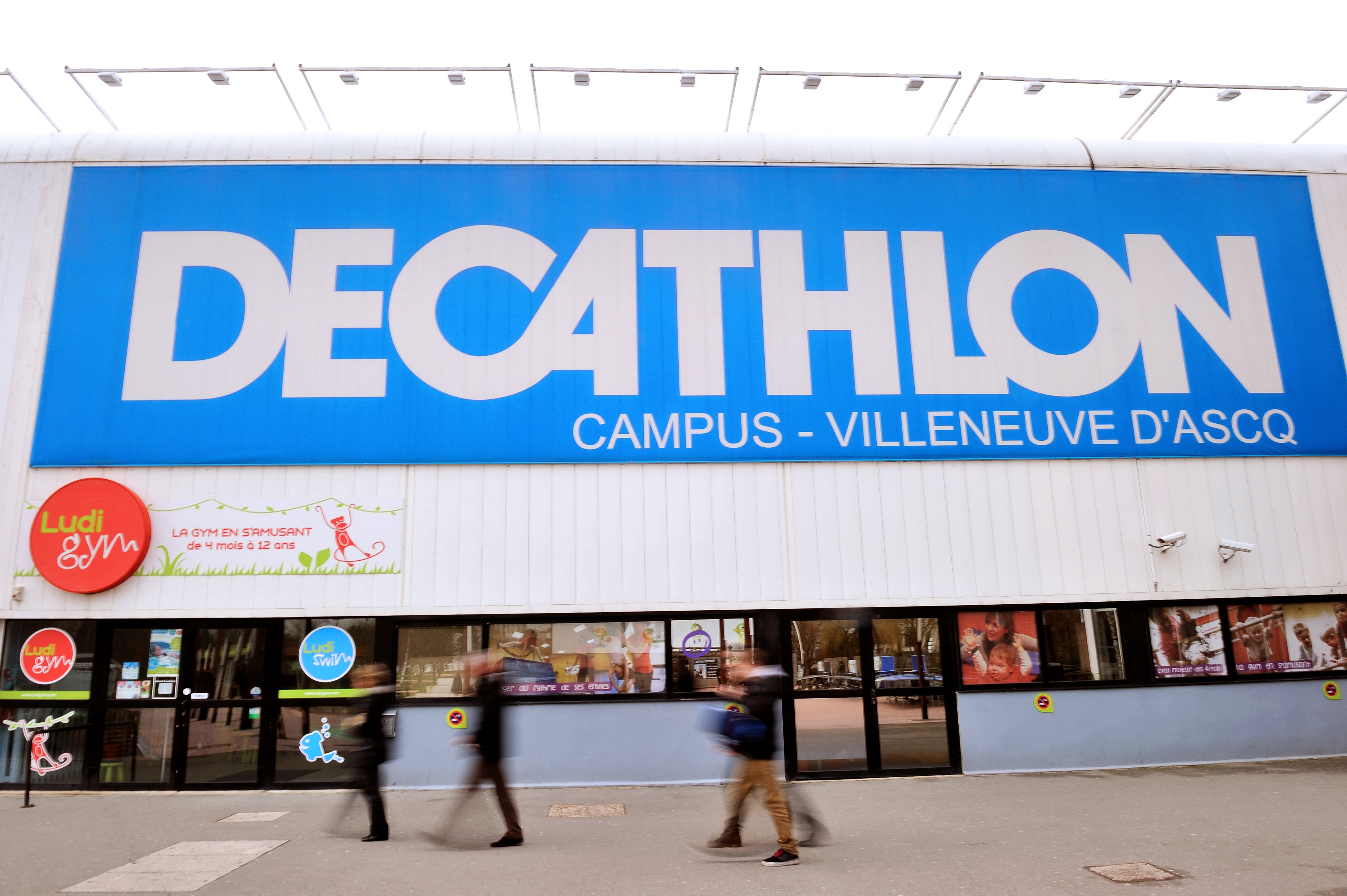 People walk in front of a Decathlon store in the French northern city of Villeneuve d'Ascq on Feb. 25, 2014