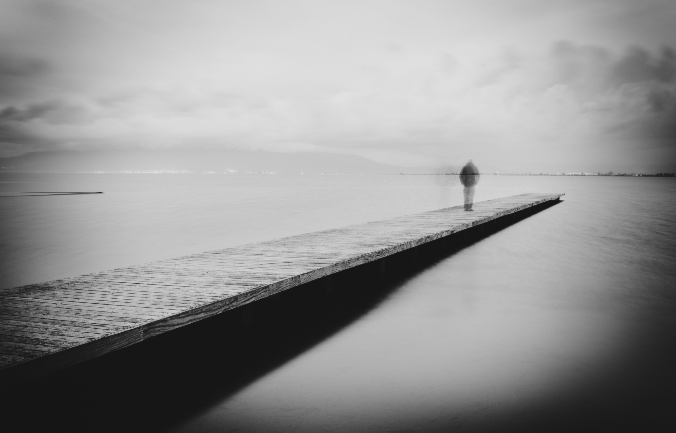 Figure of man walking on a wooden walkway in the sea.