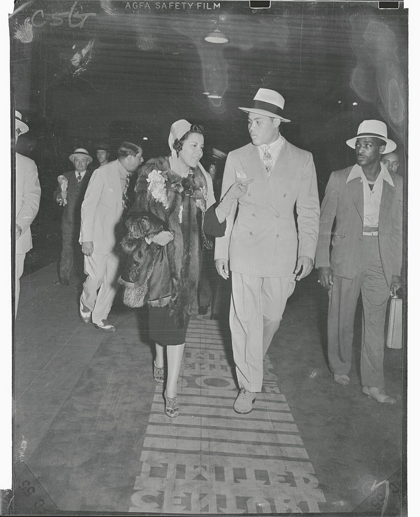 Joe Louis and his wife as they walk down to the Twentieth Century Limited in the Grand Central Station to depart for Chicago the day after Louis' one round victory over Max Schmeling in Yankee Stadium, circa 1930s.
