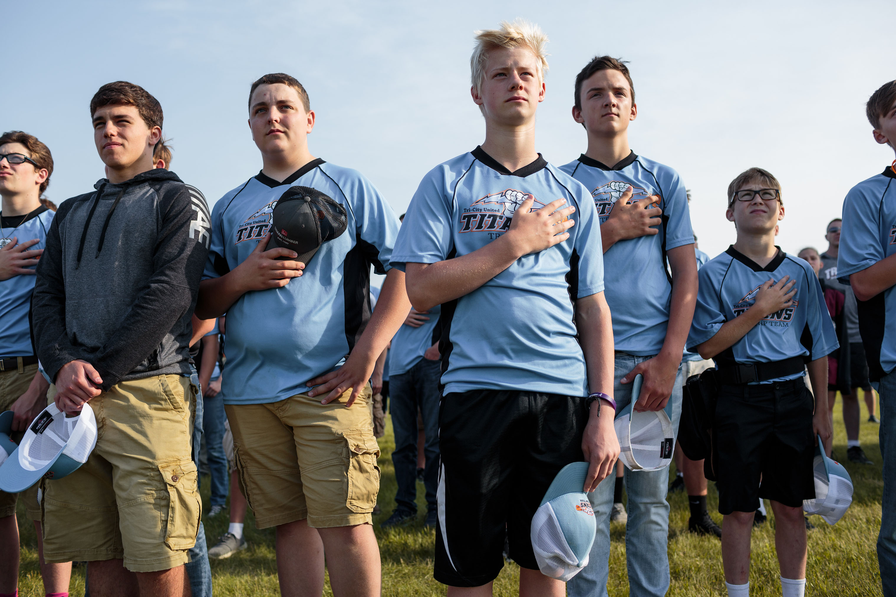 Students from Tri-City United High School stand for the Pledge of Allegiance early in the morning on June 15, 2018, before beginning to compete in the annual trap shooting championship in Alexandria, Minnesota.