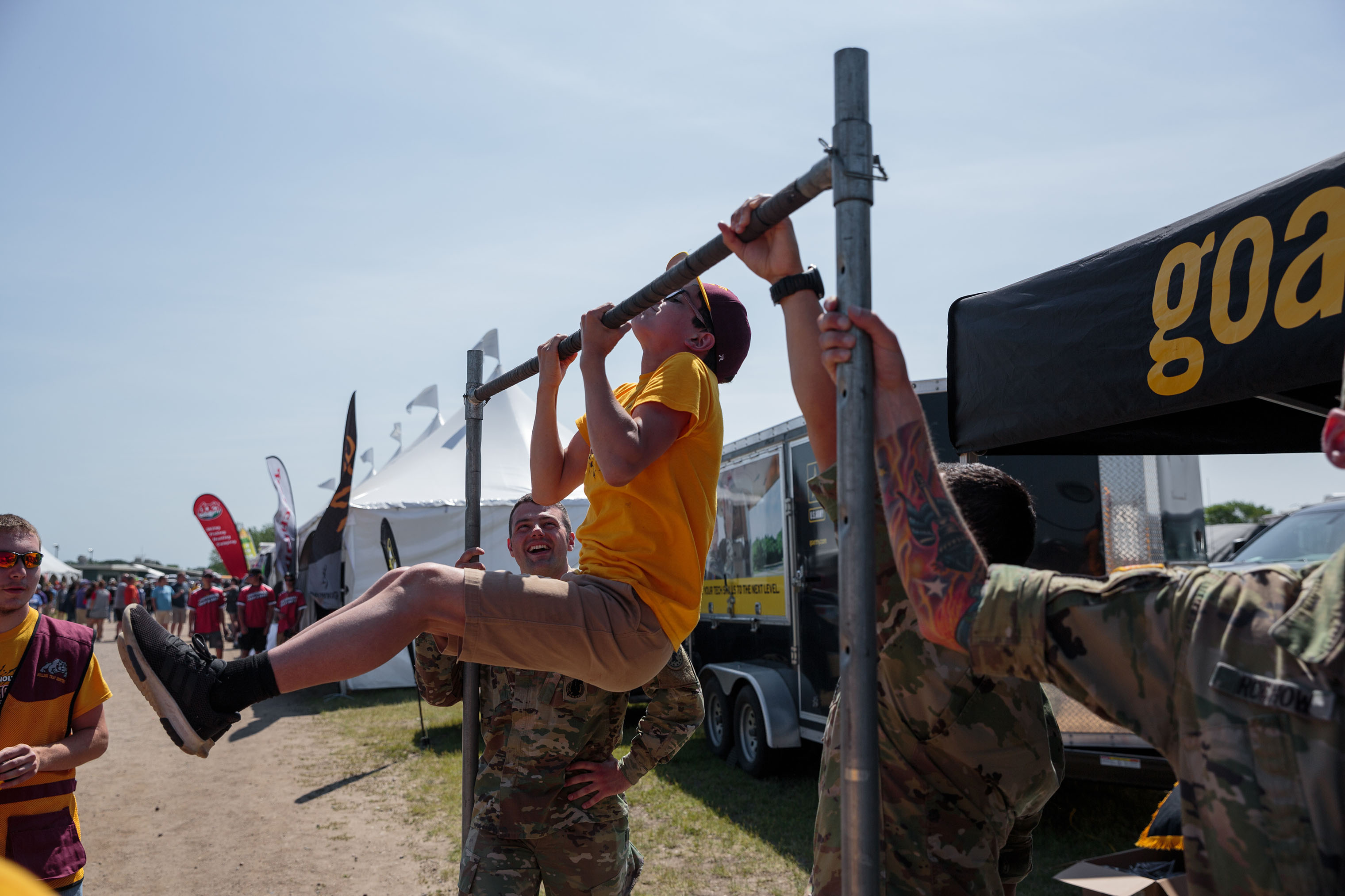 Students participate in a pull-up challenge offered by the  Go-Army  vendor tent at the annual trap shooting championship.