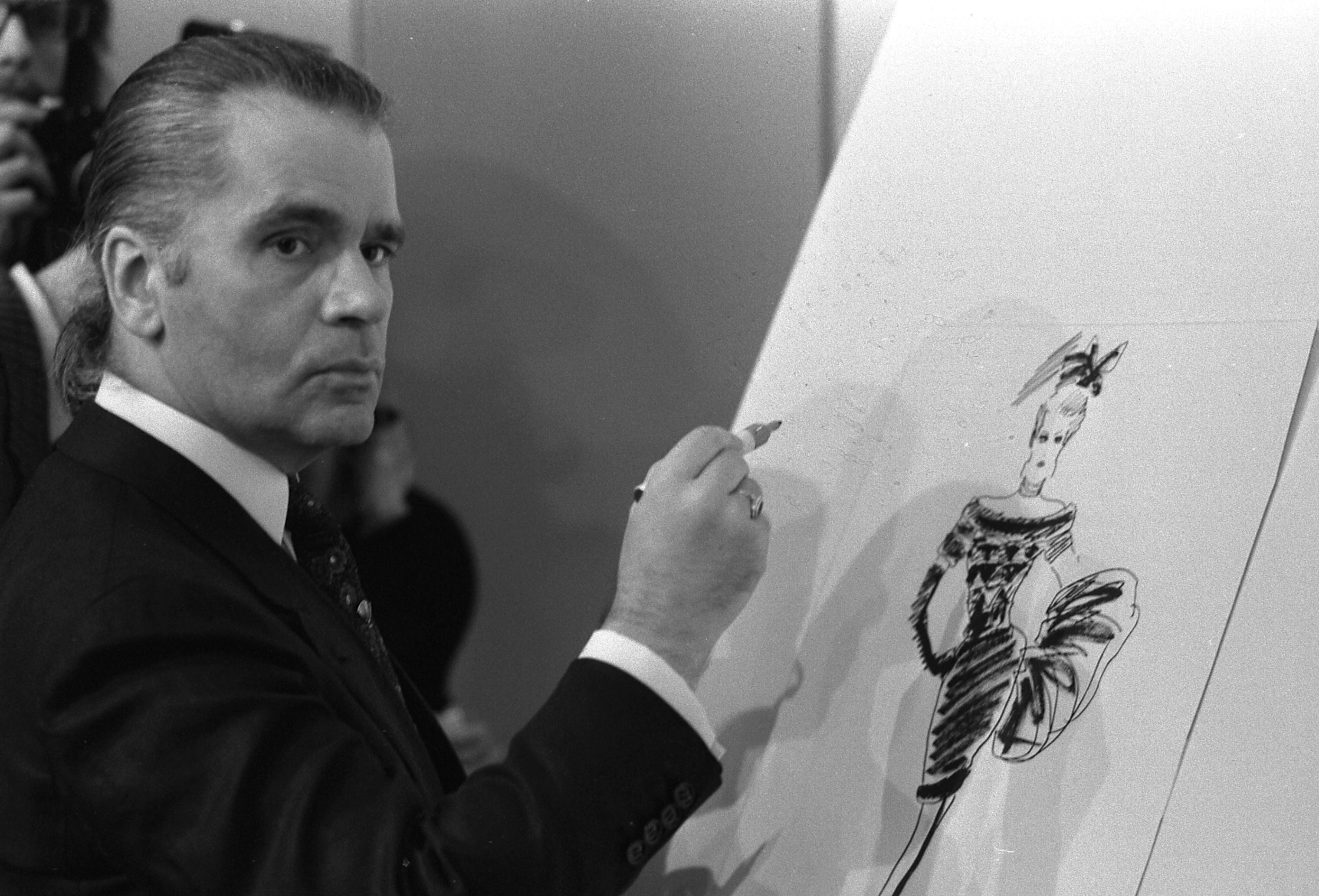 Karl Lagerfeld draws designs for textile manufacturer Klaus Steilmann, during a presentation at the Congress Center in Dusseldorf, West Germany on Sept. 4, 1987.