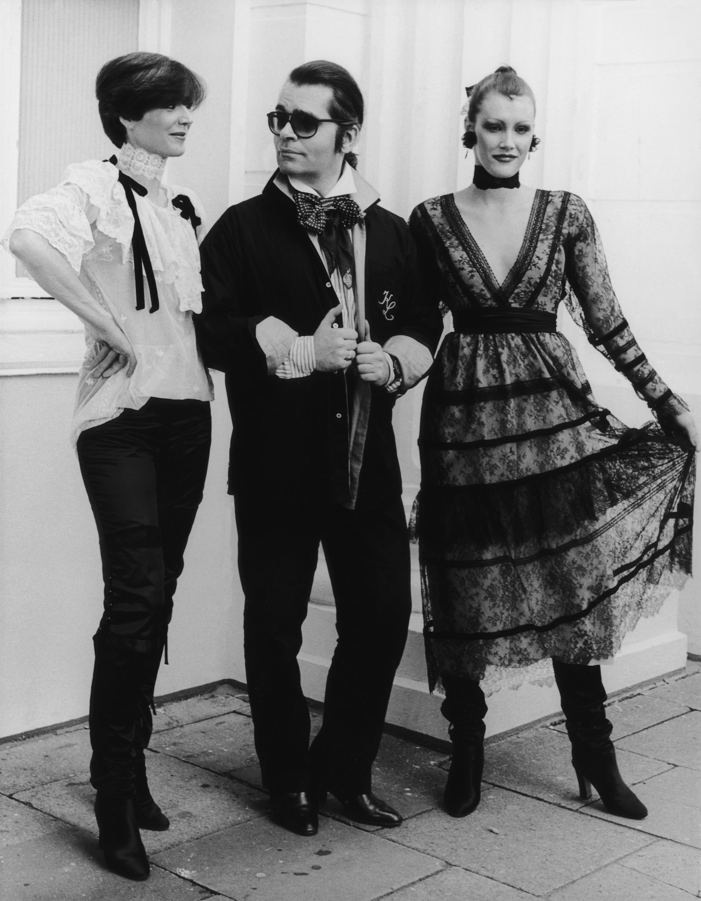 German fashion designer Karl Lagerfeld with two models, circa 1984.