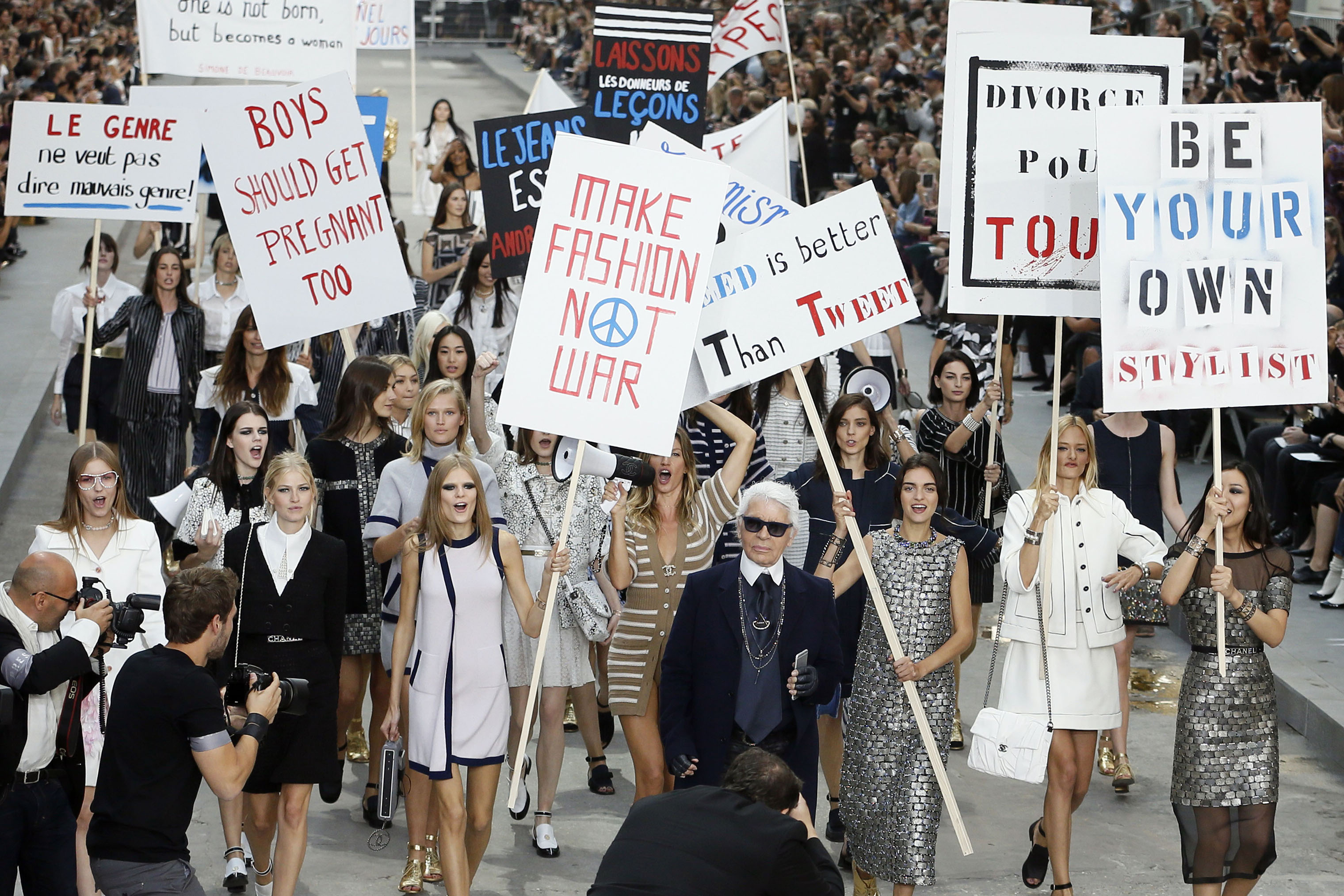 German fashion designer Karl Lagerfeld (C) acknowledges the public as Brazilian model Gisele Bundchen (back-C) speaks through a megaphone as she and other models fake a demonstration as they present creations for Chanel's 2015 Spring/Summer fashion show, on Sept. 30, 2014 at the Grand Palais in Paris.