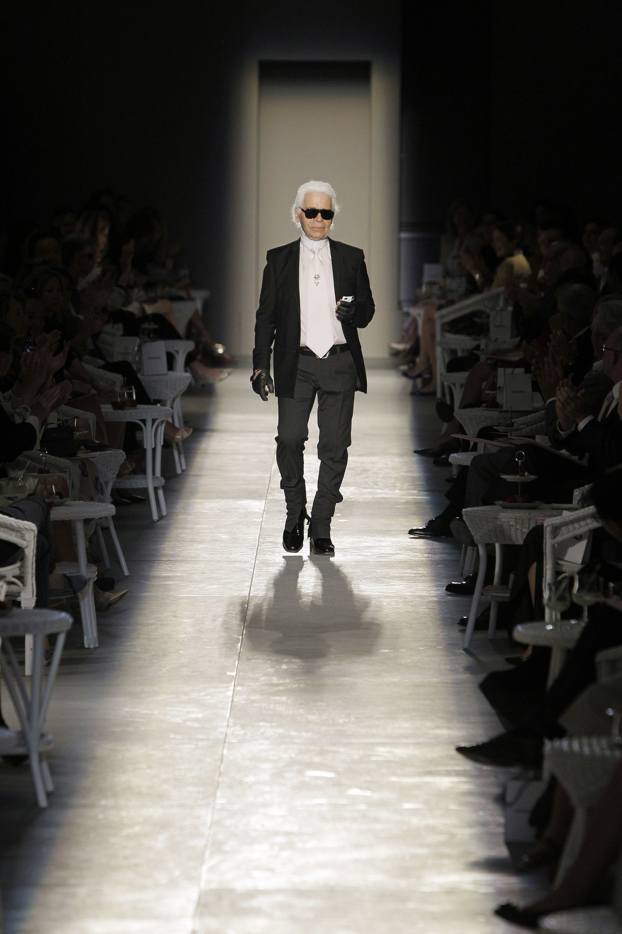 In this July 3, 2012 photo, Karl Lagerfeld acknowledges the applause of the audience at the end of his Women's Fall Winter 2013 haute couture fashion collection in Paris.