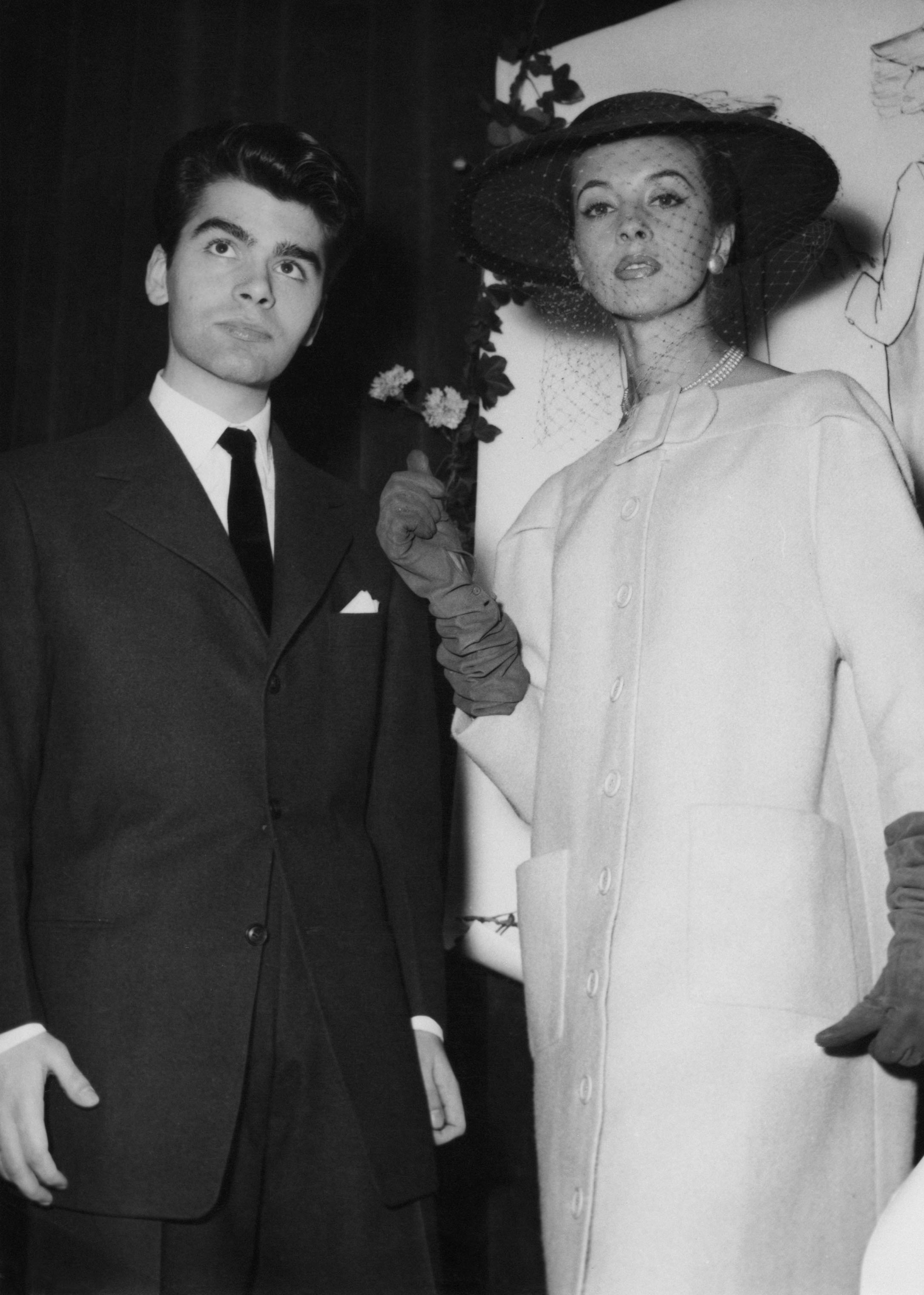 Karl Lagerfeld after winning the coats category in a design competition sponsored by the International Wool Secretariat in Paris on Dec. 14, 1954. With him is a model wearing his design.