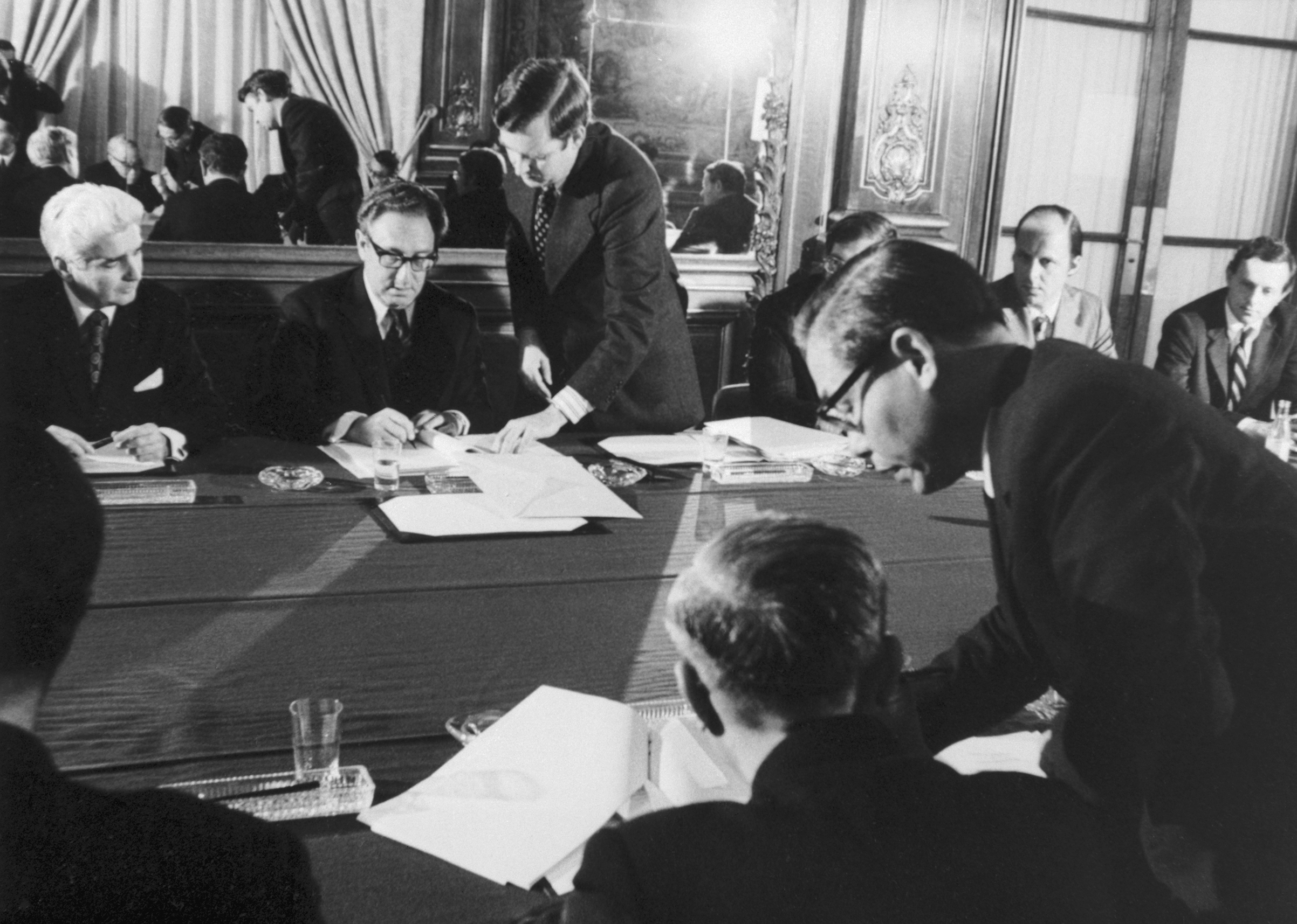 Dr. Henry Kissiinger, background, center, initialing the cease fire agreement in Paris. In the foreground Le Duc Tho affixes his signature.