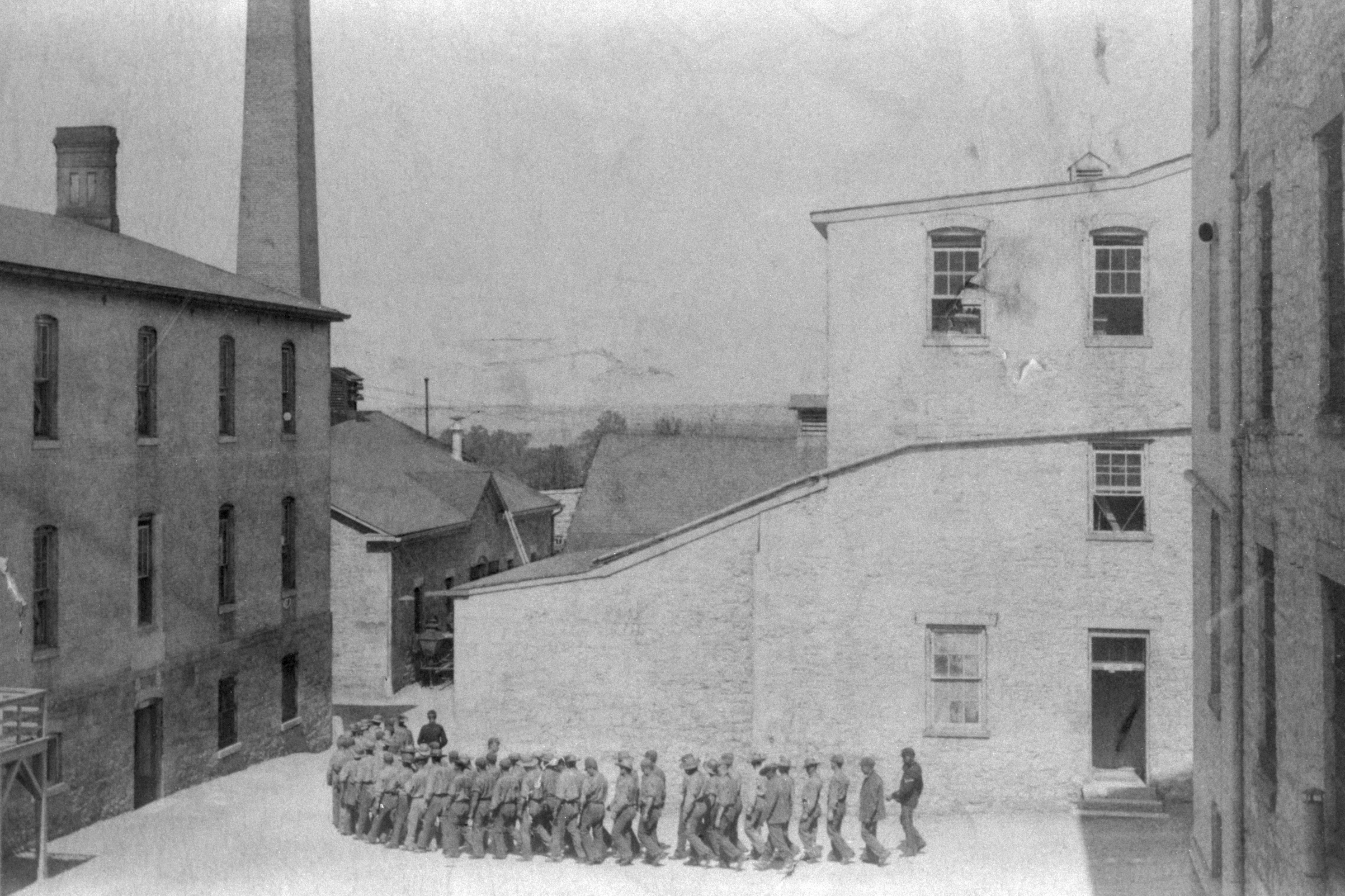 Prisoners at Fort Leavenworth Penetentiary march in a line to the mess hall for dinner ca. 1890s.