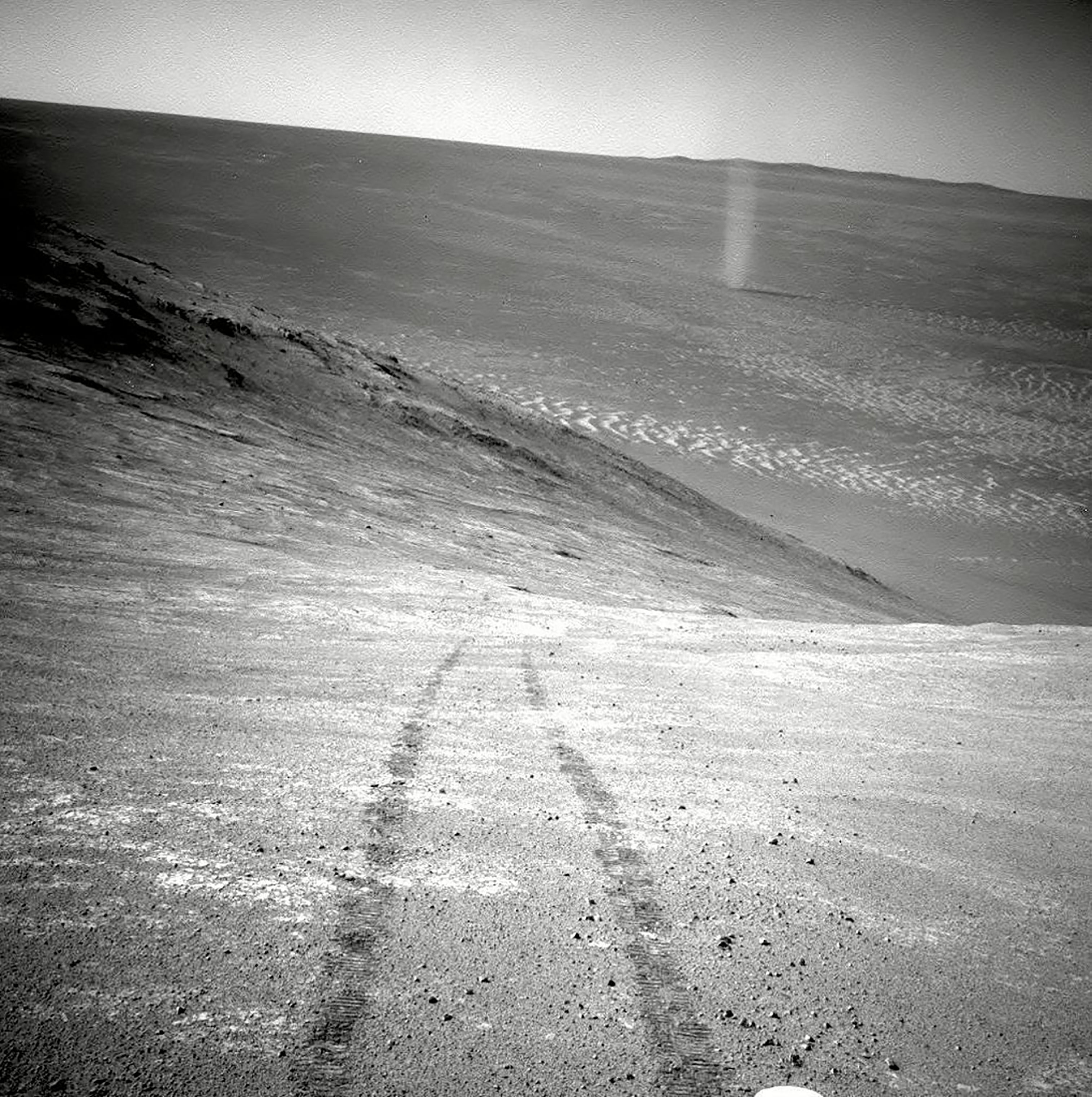 This photograph made available by NASA in March 2016 shows a dust devil in a valley on Mars, seen by the Opportunity rover perched on a ridge. The view looks back at the rover's tracks leading up the north-facing slope of  Knudsen Ridge.