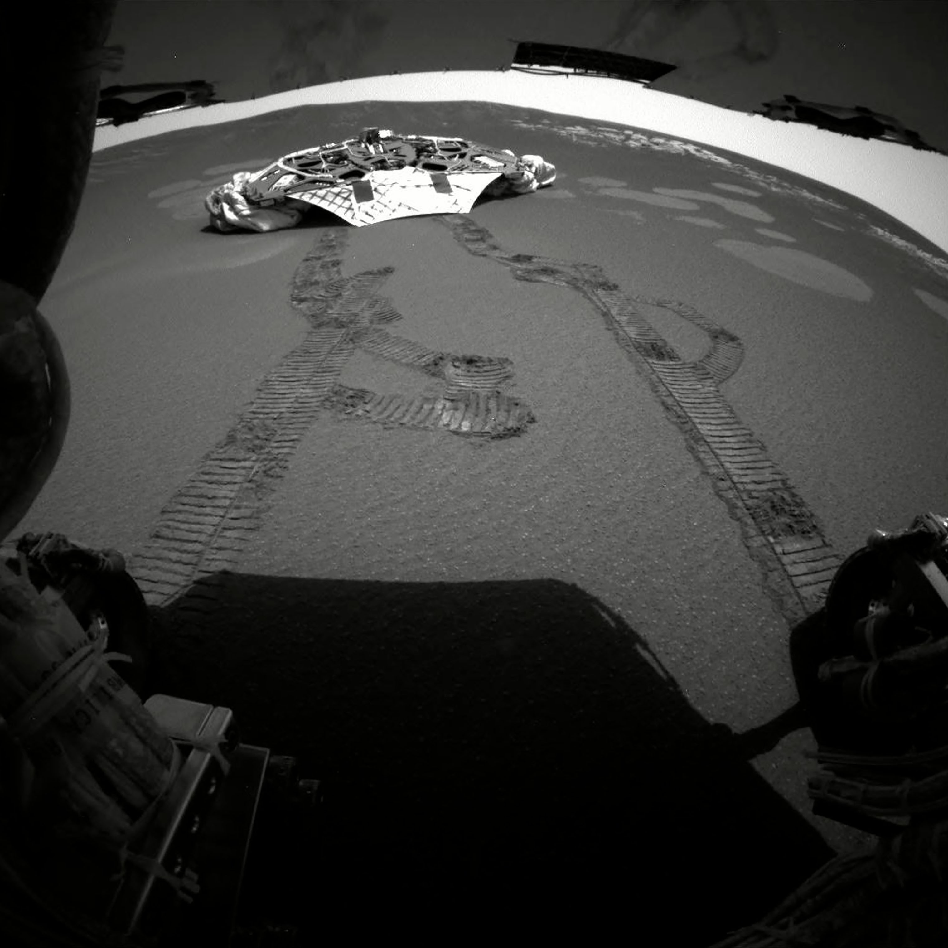This photograph made by one of the rear hazard-avoidance cameras on Opportunity rover in February 2004 shows its landing platform, with freshly made tracks leading away from it.