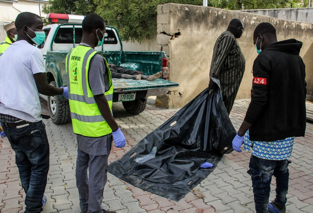 Officials load the body of a victim to the general hospital mortuary on a street of the Jiddari Polo neighbourhood of the northeastern Nigeria city of Maiduguri, on Februray 16, 2019 where Boko Haram fighters shot residents while two suicide bombers blew themselves up, killing eight people.