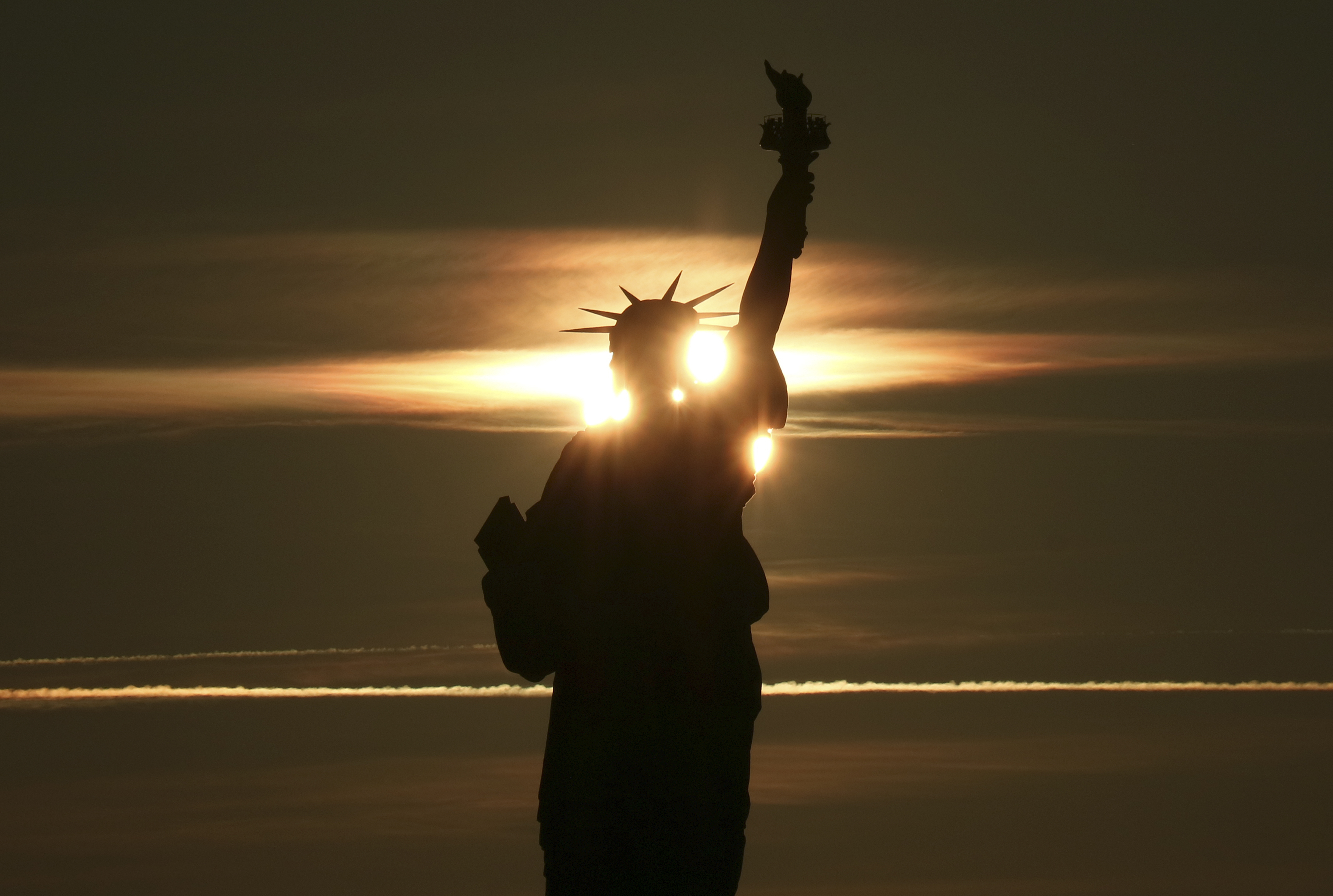 The sun rises behind the Statue of Liberty in New York City on December 29, 2018 as seen from Liberty State Park in Jersey City, New Jersey.