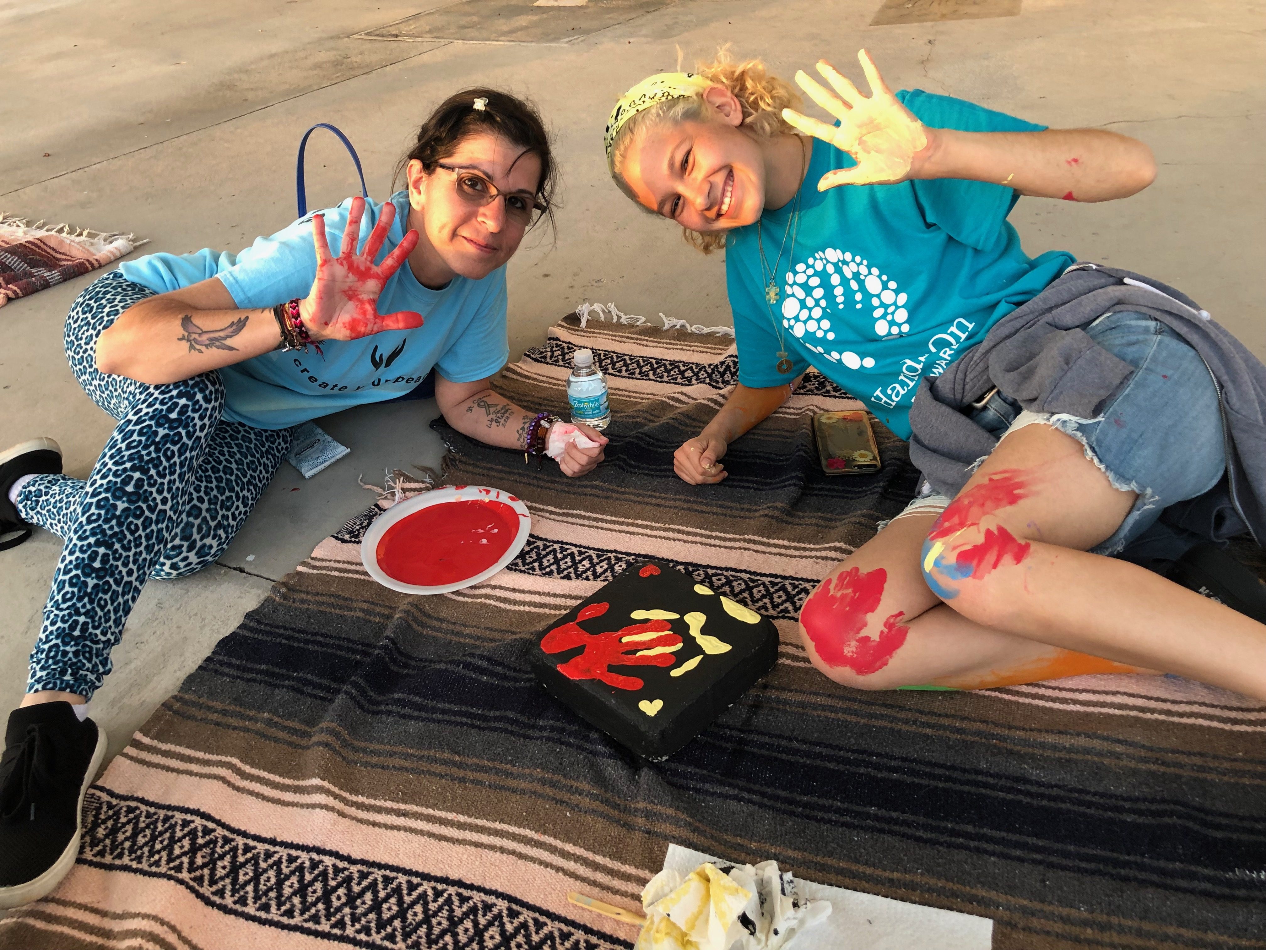 Stoneman Douglas teacher Ronit Reoven (left) and senior Tori Gonzalez (right) paint ceramic tiles for Project Grow Love, a garden memorial they built outside the school.