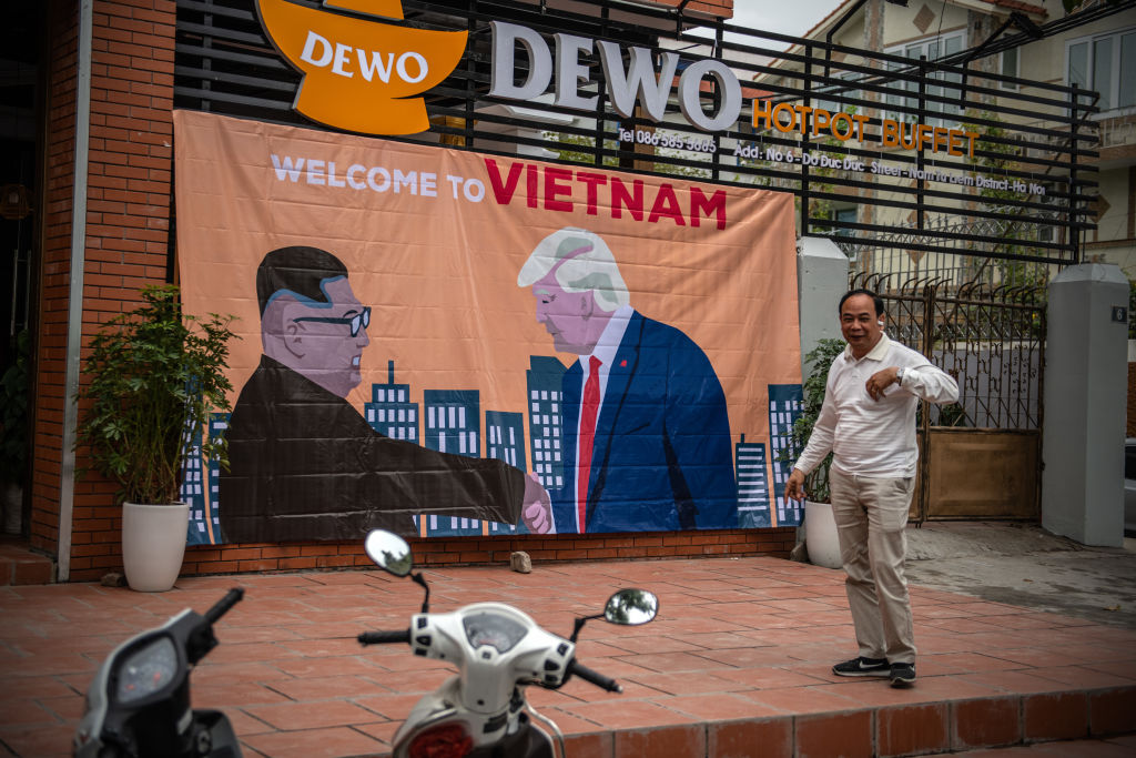 A man pauses by a banner showing U.S President Donald Trump and North Korean leader Kim Jong Un shaking hands next to the words 'Welcome to Vietnam' hung opposite the Marriott Hotel where President Trump is expected to stay during the forthcoming DPRK-USA summit in Hanoi, Vietnam on Feb. 25, 2019