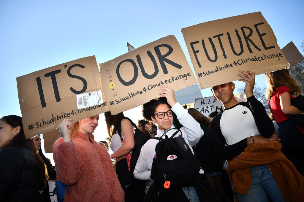 Young demonstrators hold placards as they attend a climate change protest organized by  Youth Strike 4 Climate  opposite the Houses of Parliament in central London on February 15, 2019.