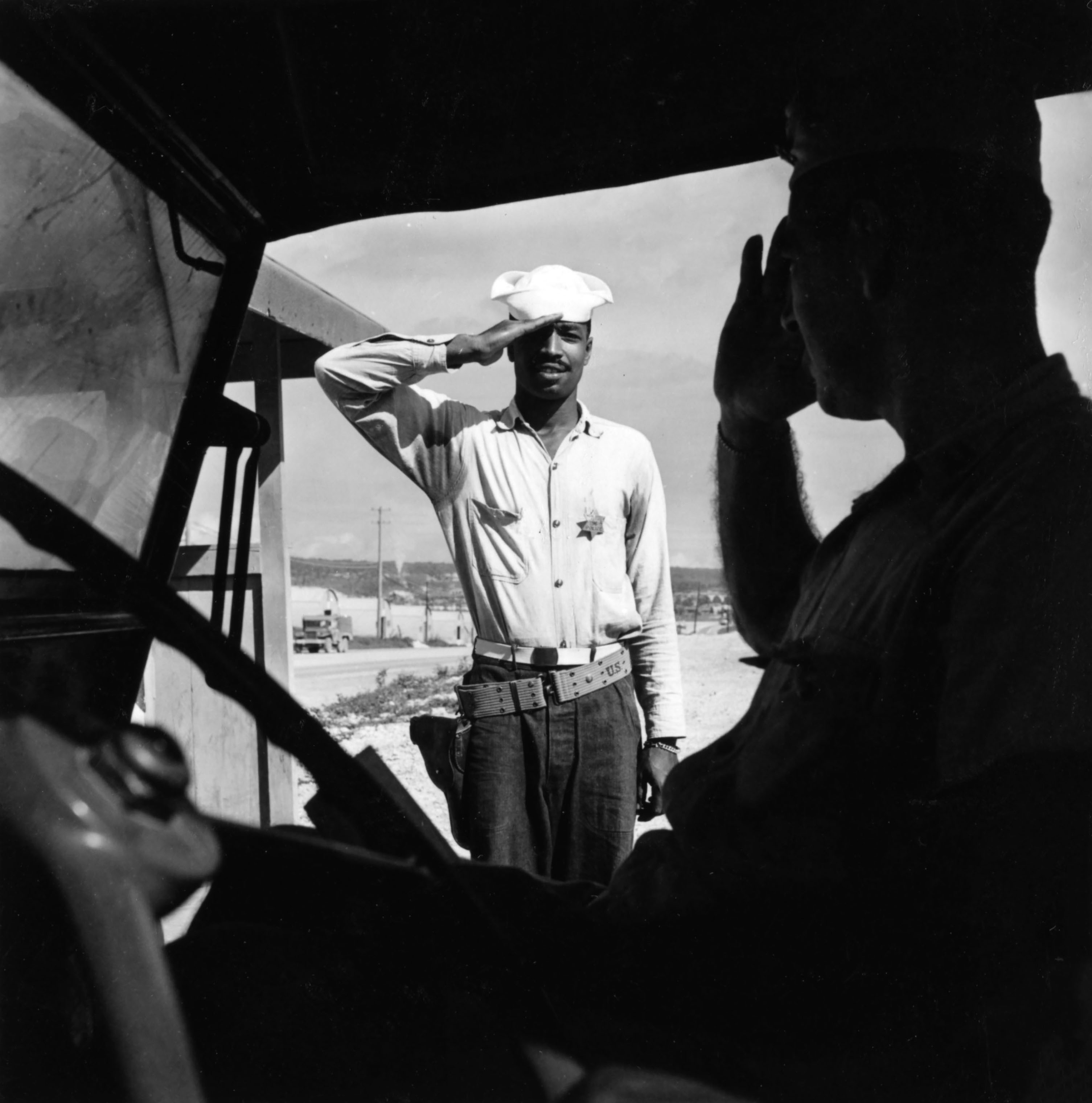 A sailor assigned to work as a laborer at the U.S. Naval Supply Depot on Guam saluting an officer.