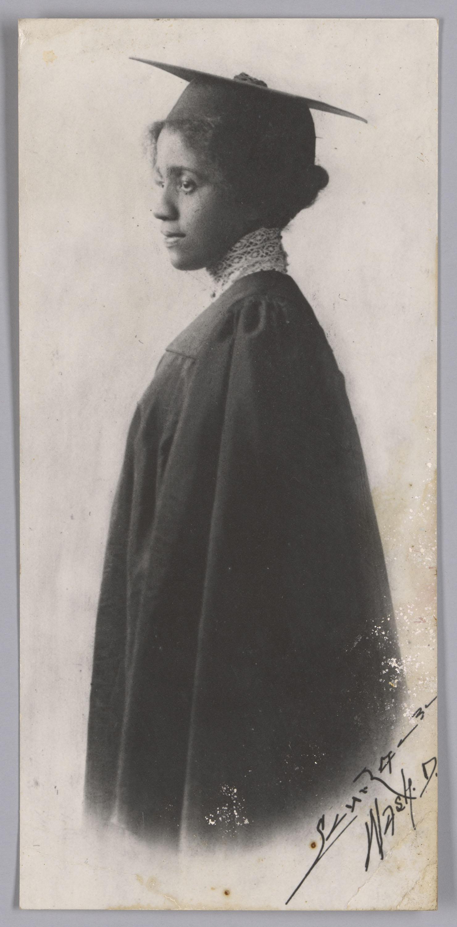 Black and white portrait of a woman in graduation attire. The woman is standing with the left side of her body faceing the camera and is wearing a graduation cap and gown. Her high neck lace blouse is visible underneath her gown. Taken by Addison N. Scurlock, 1900s-1910s. The Scurlock Studio in Washington, D.C., served the city's black community, documenting the milestone moments of their lives.