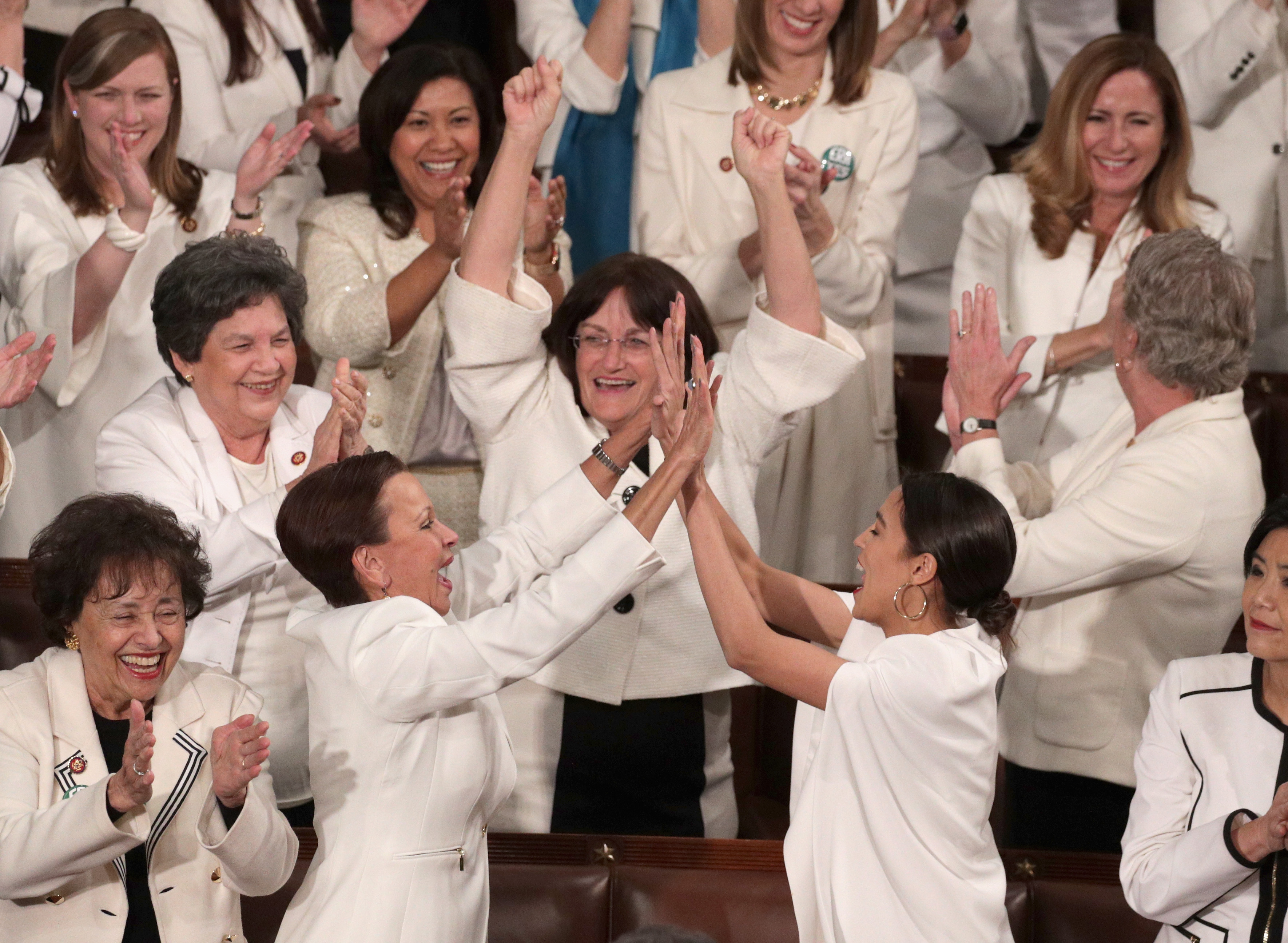 Rep. Alexandria Ocasio-Cortez (D-NY) and other female lawmakers cheer during President Donald Trump's State of the Union address in the chamber of the U.S. House of Representatives at the U.S. Capitol Building on February 5, 2019 in Washington, D.C.