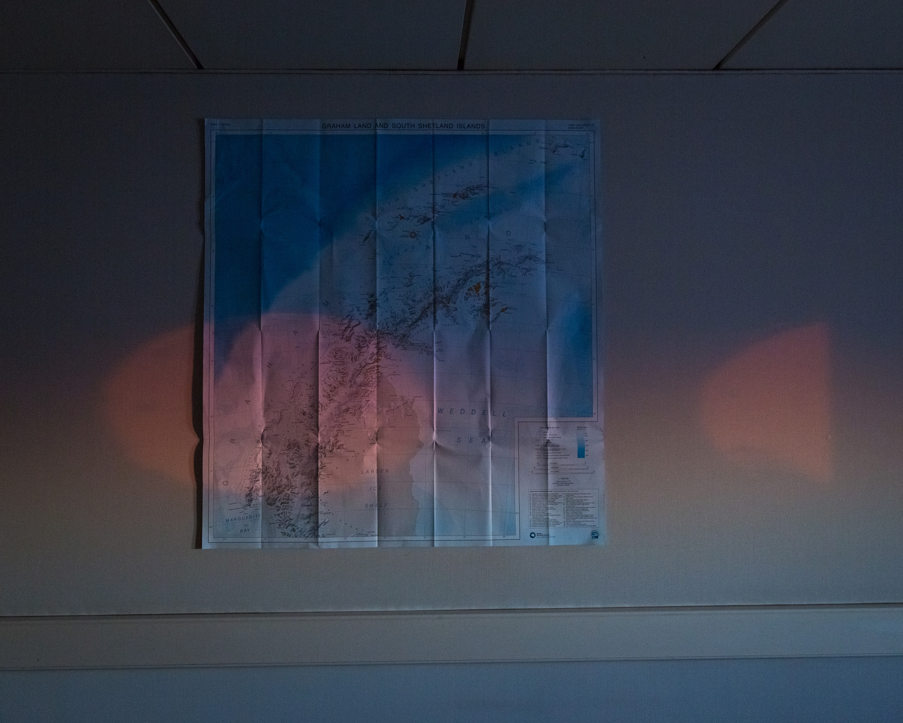 An Antarctic sunset glows through the portholes of a bedroom. On the wall is a map of the Antarctic Peninsula.
