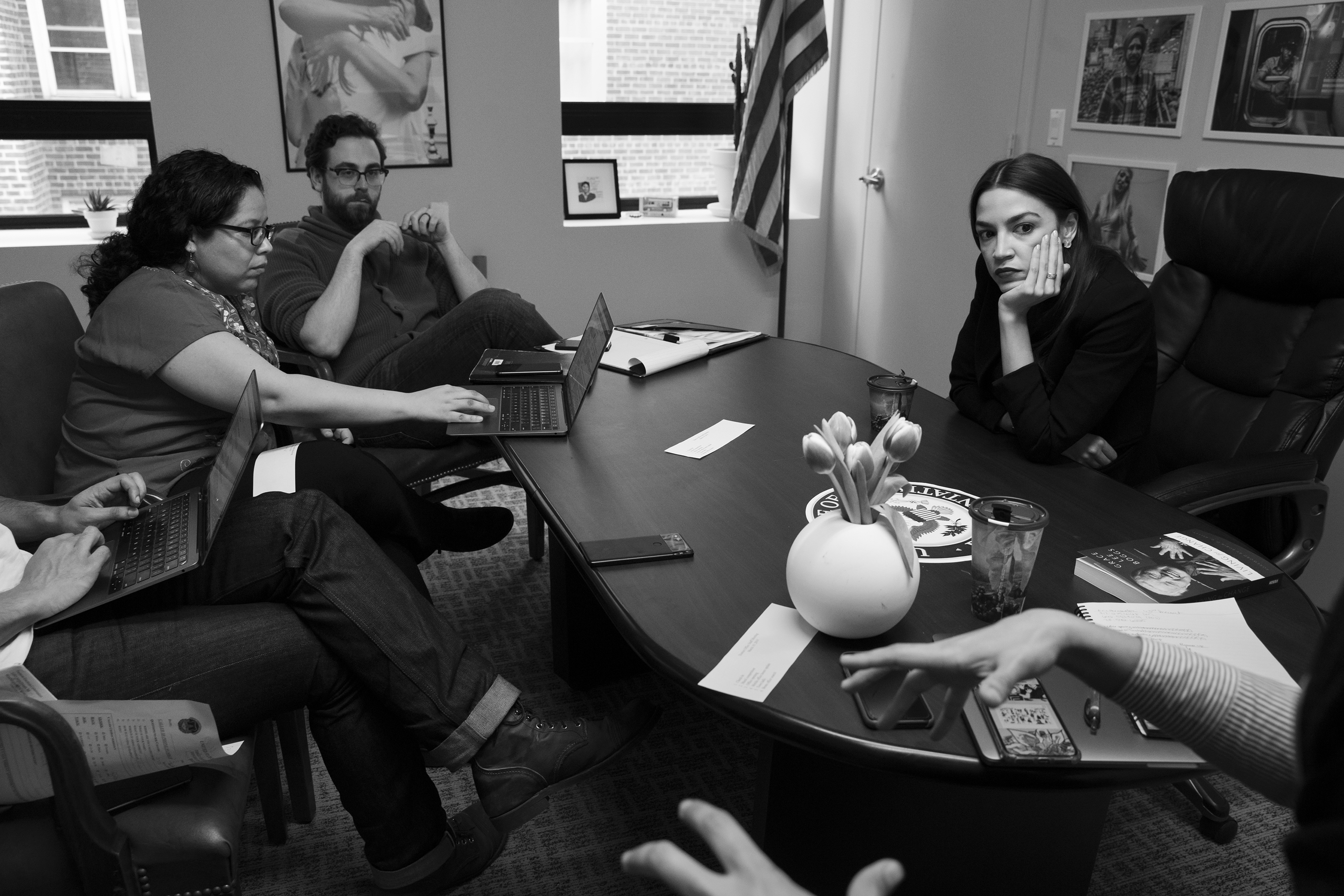 The staff and the boss meet in their Queens district office.