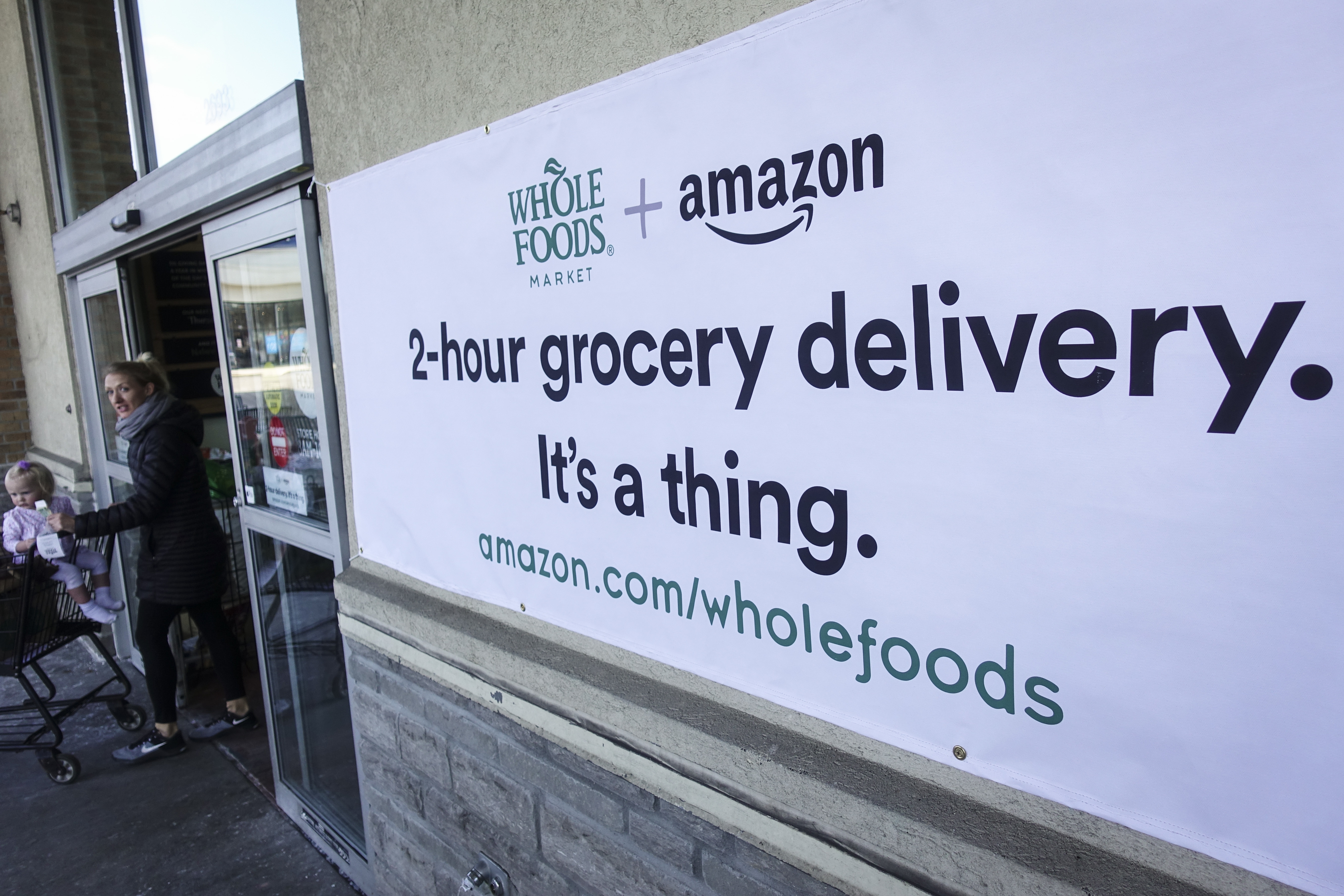 On Feb. 8, 2018 a sign promotes the Amazon Prime Now delivery service is displayed outside a Whole Foods store, in Cincinnati. Amazon is planning on opening dozens of grocery stores in U.S. cities the Wall Street Journal reported on Mar. 1, 2019.