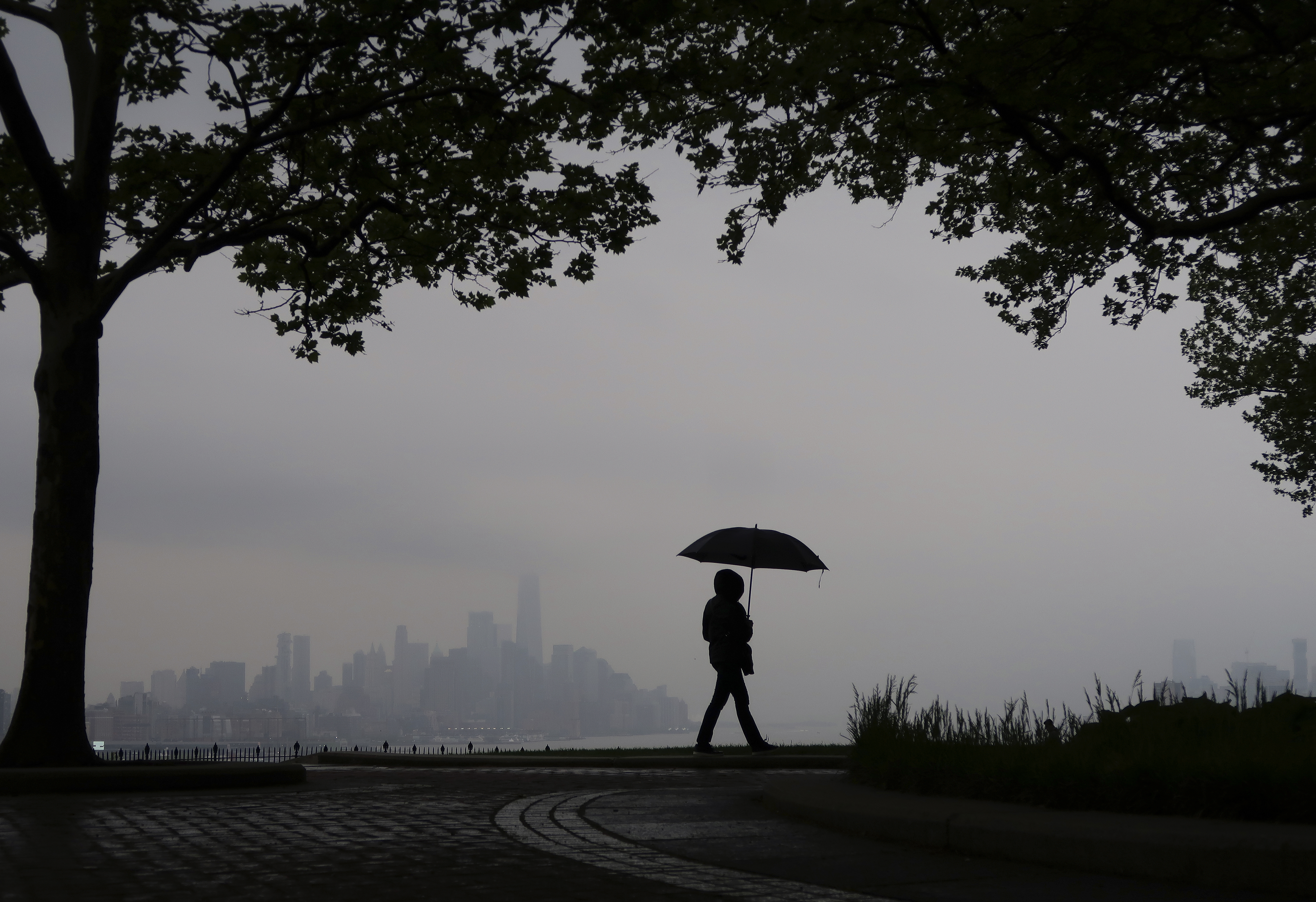A person walks in front of the skyline of lower Manhattan and One World Trade Center on a rainy day in New York City on May 12, 2018 as seen from Weehawken, New Jersey.