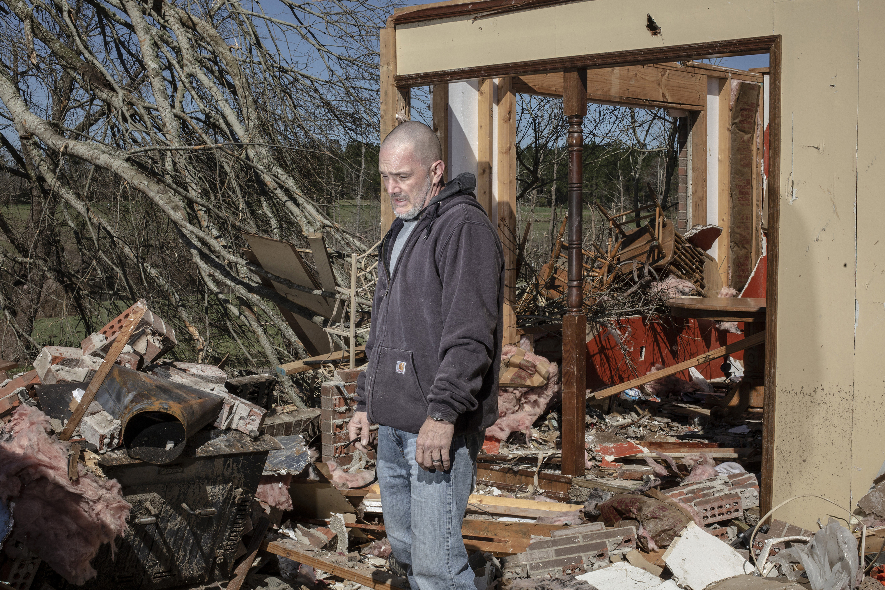 Scott Kimbro poses for a portrait while helping friends sort through the debris of their home after a tornado passed over, killing several people and destroying homes in Beauregard, Alabama, on March 4, 2019.