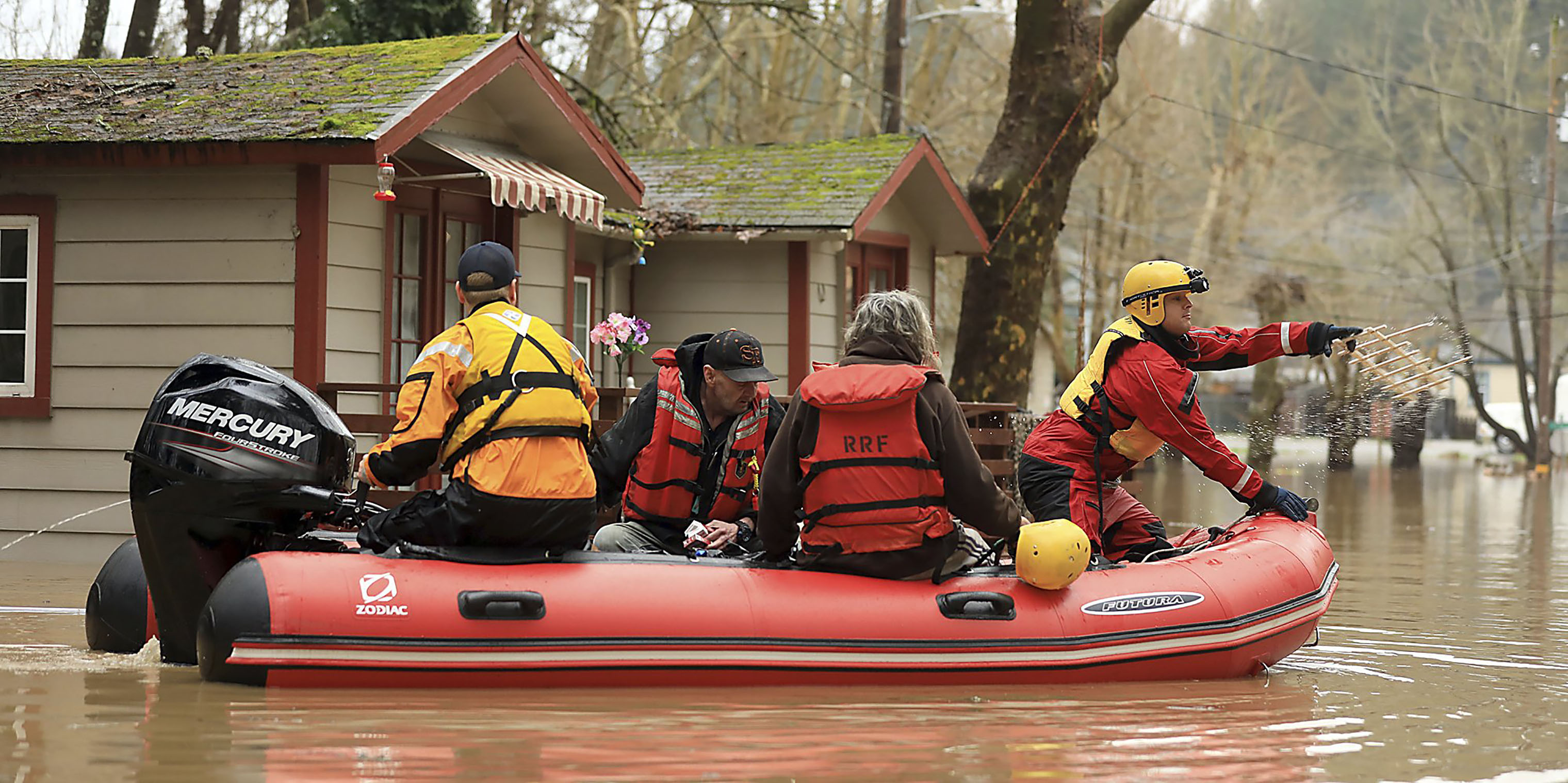 Ryan Lance, front, and Anthony Nash of the Russian River Fire Protection District swift water rescue team help residents of Sycamore Court Apartment Wednesday, Feb. 27, 2019, in lower Guerneville, California.