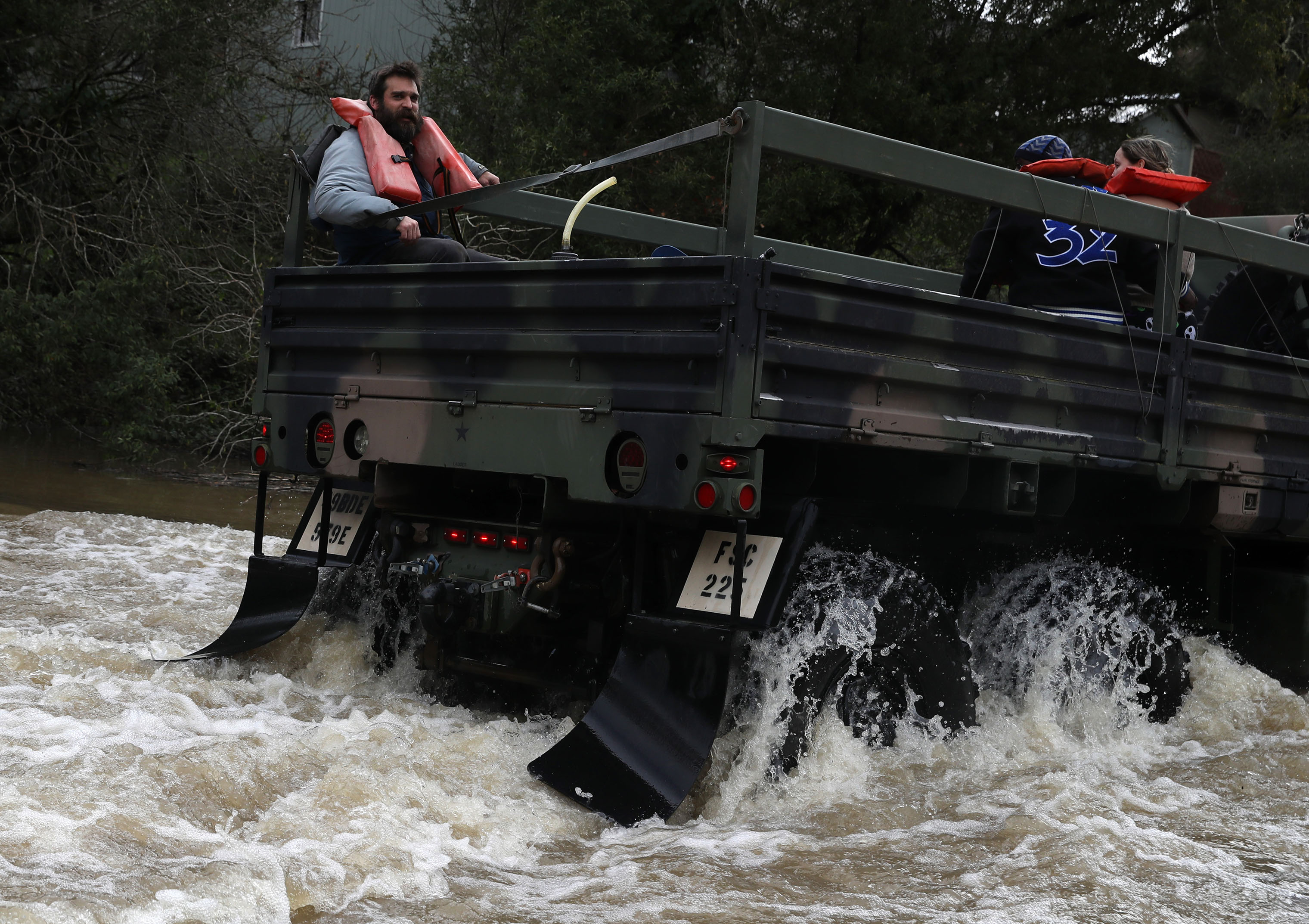 Rescue workers evacuate residents on a truck as they drive through a flooded neighborhood on Feb. 27, 2019 in Forestville, California.